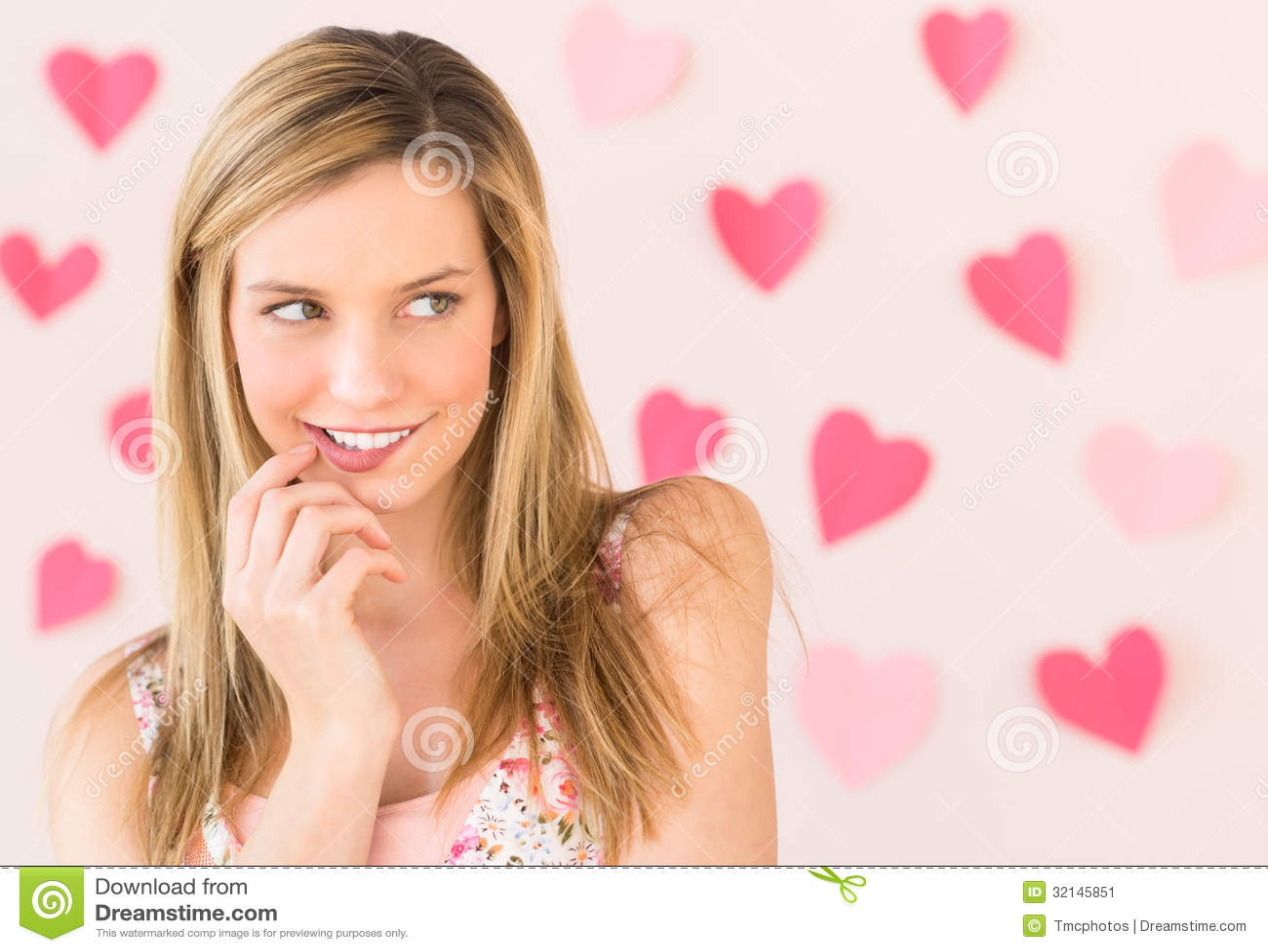 Χείλι δαγκώματος γυναικών με διαμορφωμένα τα καρδιά έγγραφα ενάντια σε χρωματισμένο Backgr