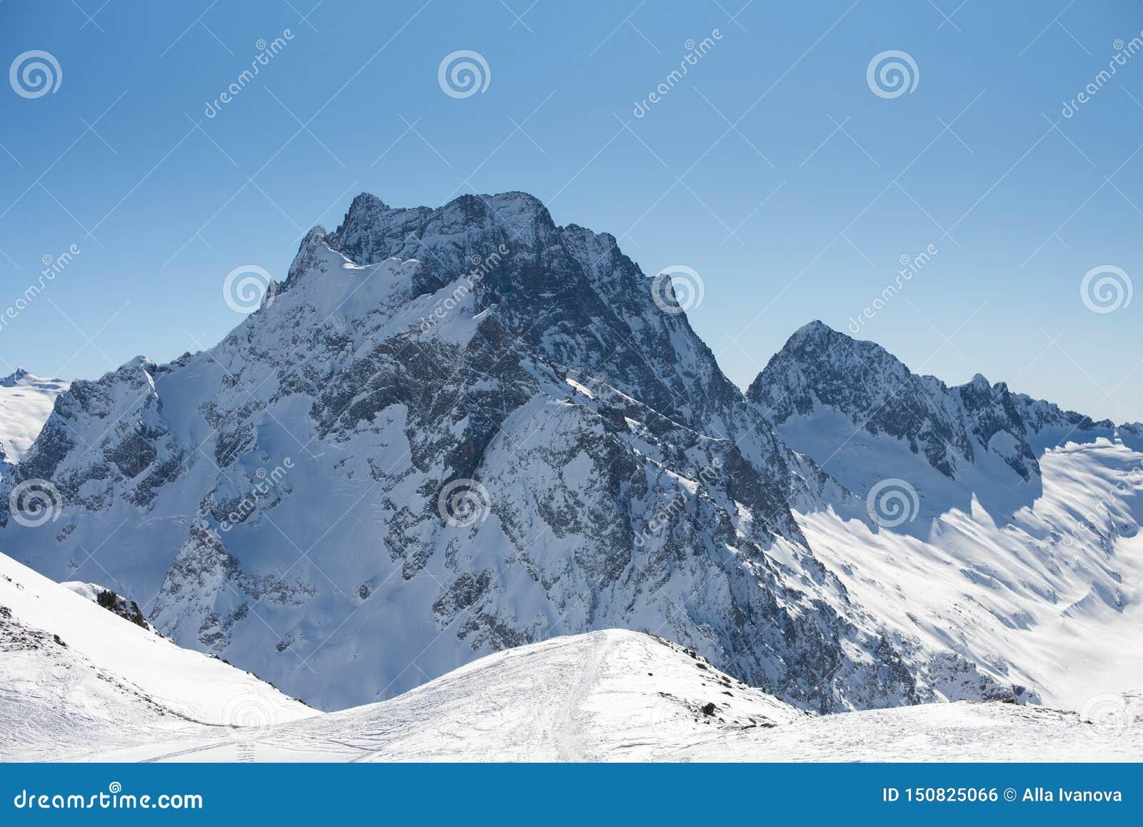 Χειμερινά βουνά με το χιόνι και το μπλε ουρανό στη συμπαθητική ημέρα ήλιων Έννοια χιονοδρομικών κέντρων και αθλητισμού Βουνά Καύκ