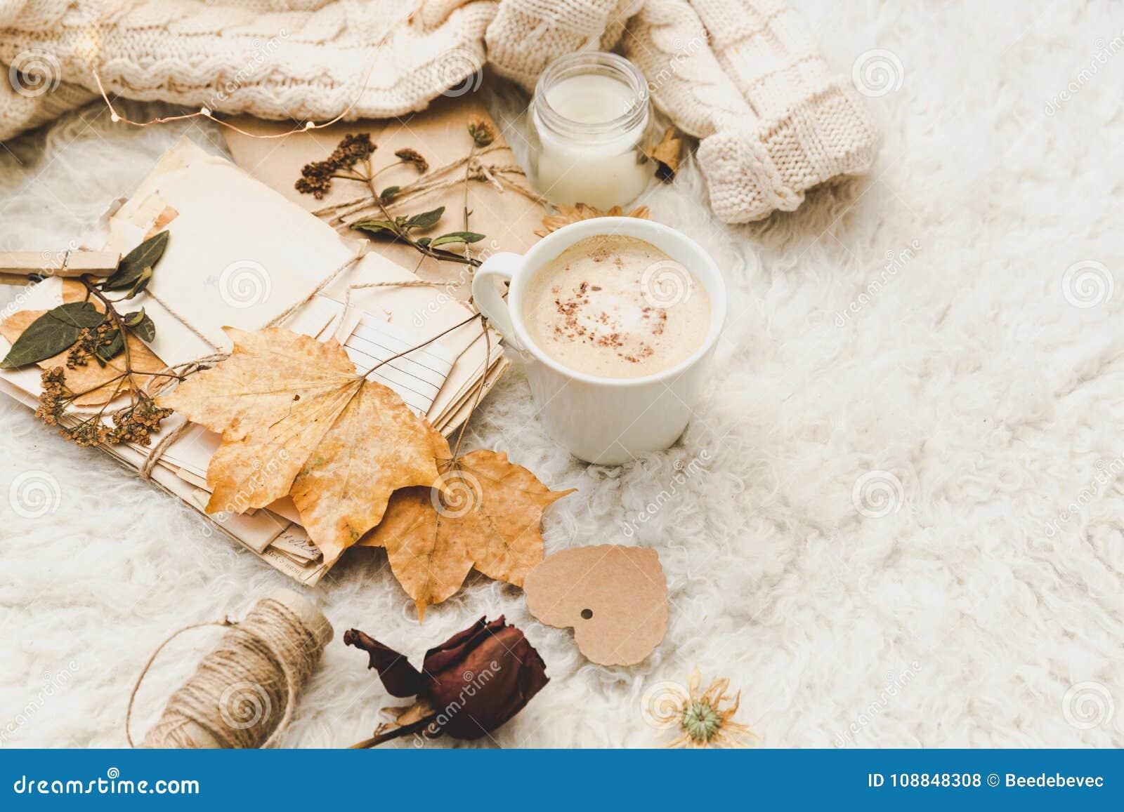 Χειμερινό άνετο υπόβαθρο με το φλιτζάνι του καφέ, το θερμό πουλόβερ και τις παλαιές επιστολές Επίπεδος βάλτε
