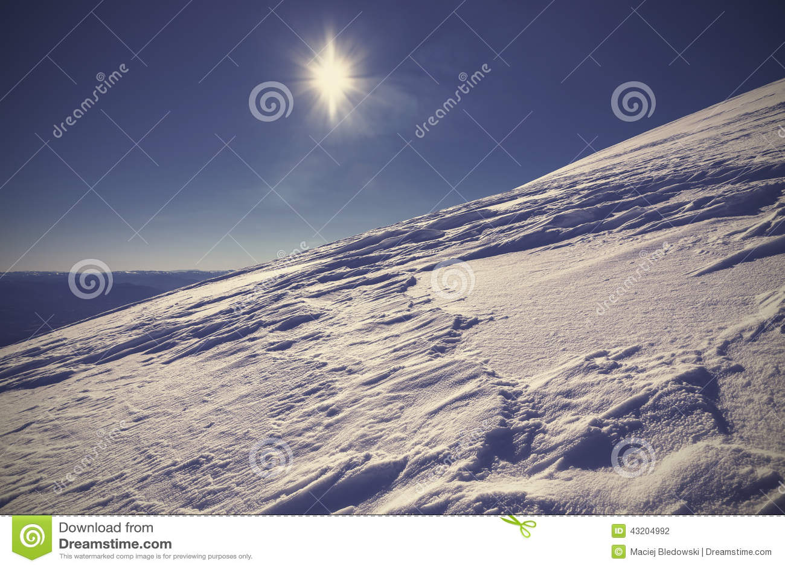 Χειμερινό βουνό που καλύπτεται με το χιόνι ενάντια στον ήλιο