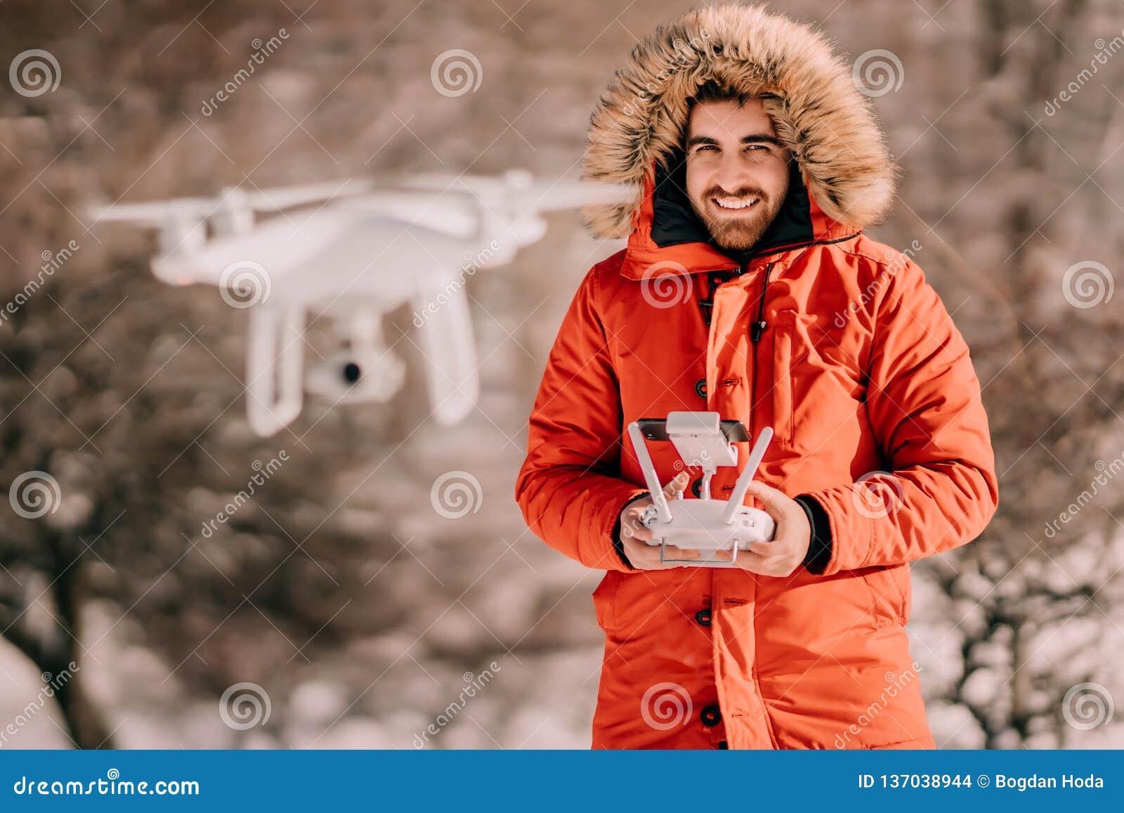 Χειμερινό πορτρέτο του ατόμου που φορά το θερμό πετώντας κηφήνα σακακιών, οδηγώντας το άσπρο quadcopter