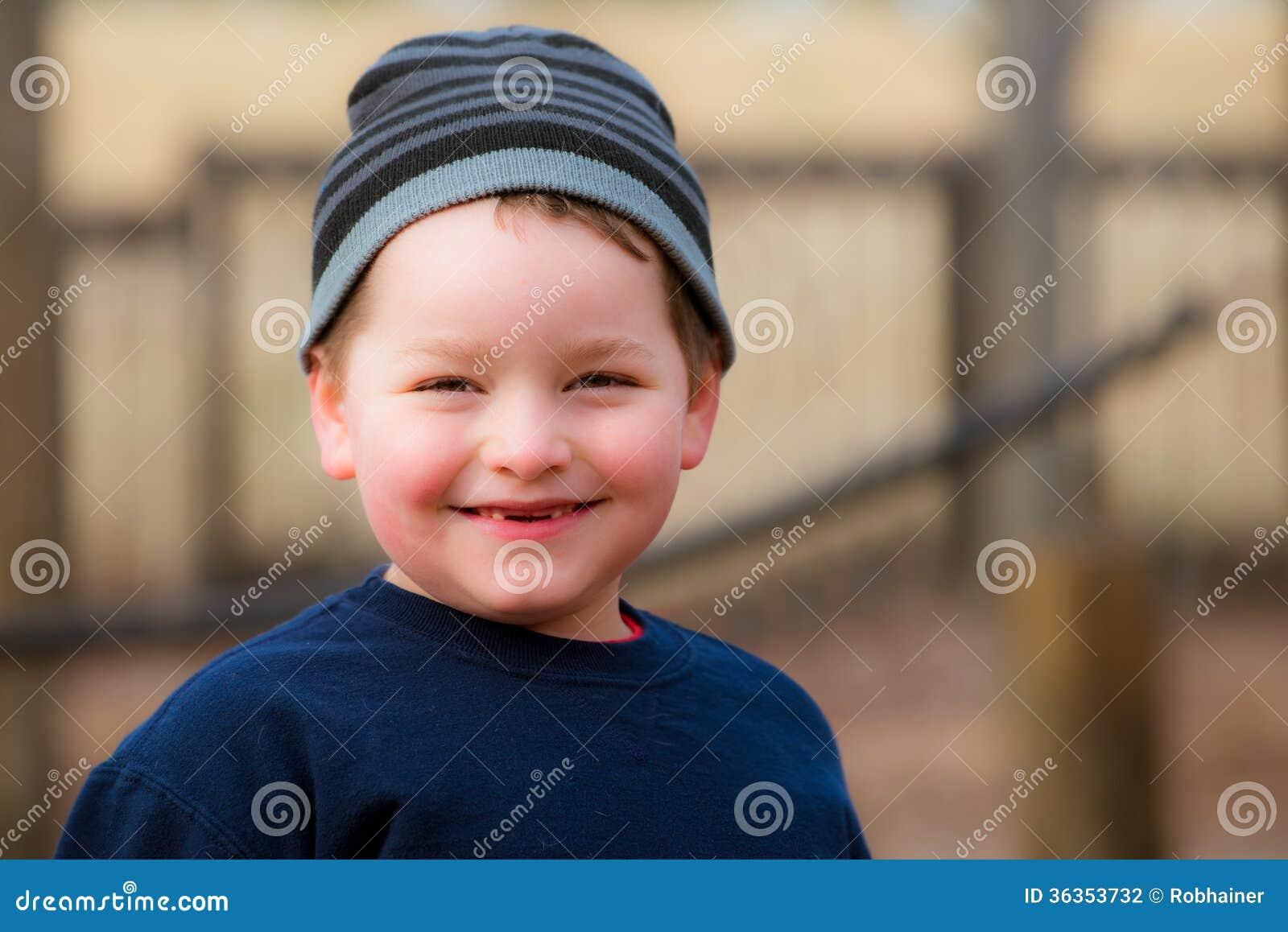 Χειμερινό πορτρέτο του ευτυχούς αγοριού στην παιδική χαρά