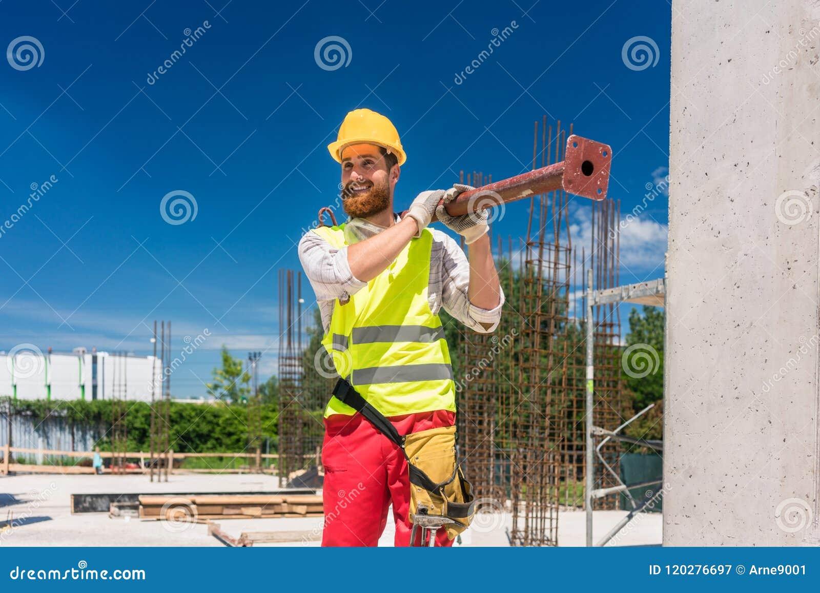 Χειροποίητος εργαζόμενος που φέρνει έναν βαρύ μεταλλικό φραγμό κατά τη διάρκεια της εργασίας