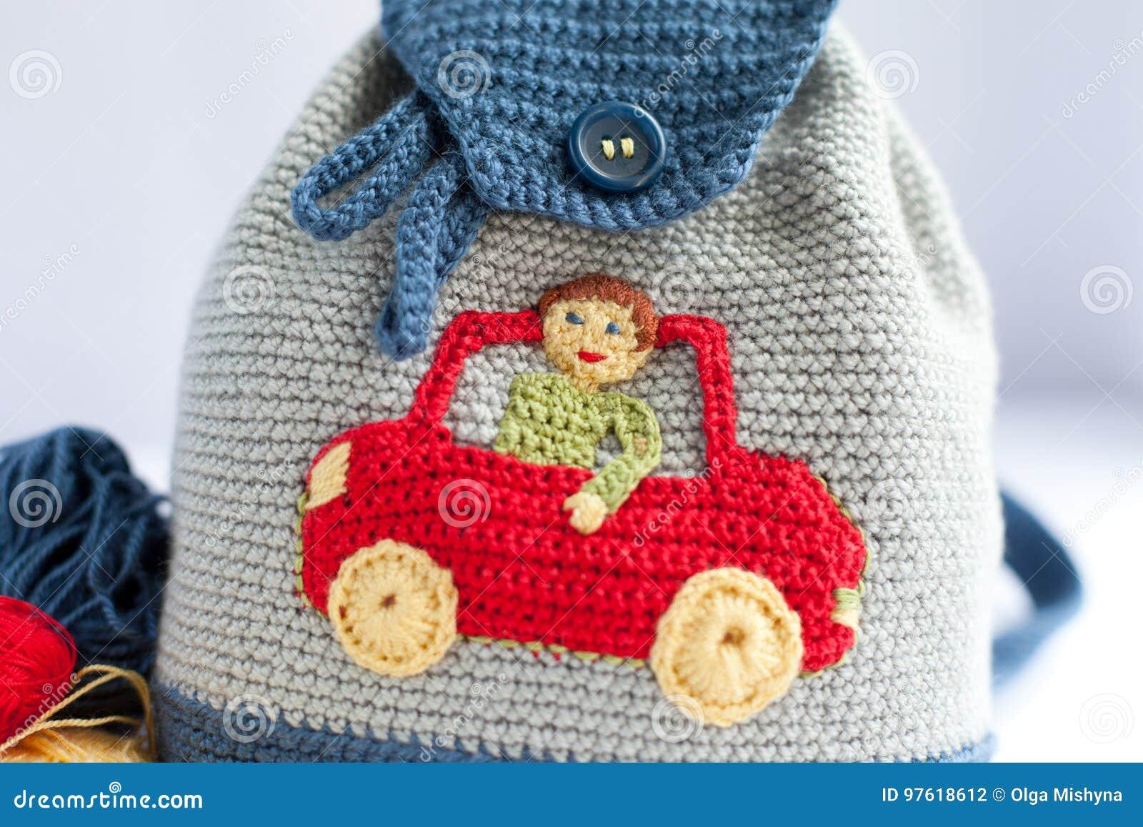 d2d8935c84 Χειροποίητο πλεκτό σακίδιο πλάτης και ένα καπέλο για ένα παιδί στο άσπρο  υπόβαθρο