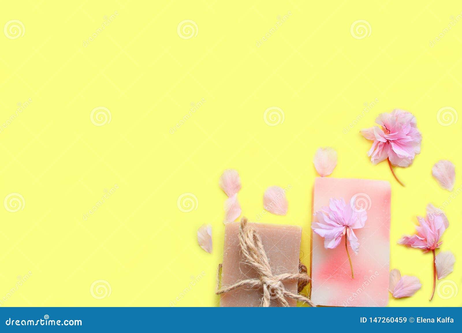 Χειροποίητο σαπούνι σε ένα κίτρινο υπόβαθρο, πέταλα λουλουδιών Διάστημα για ένα κείμενο