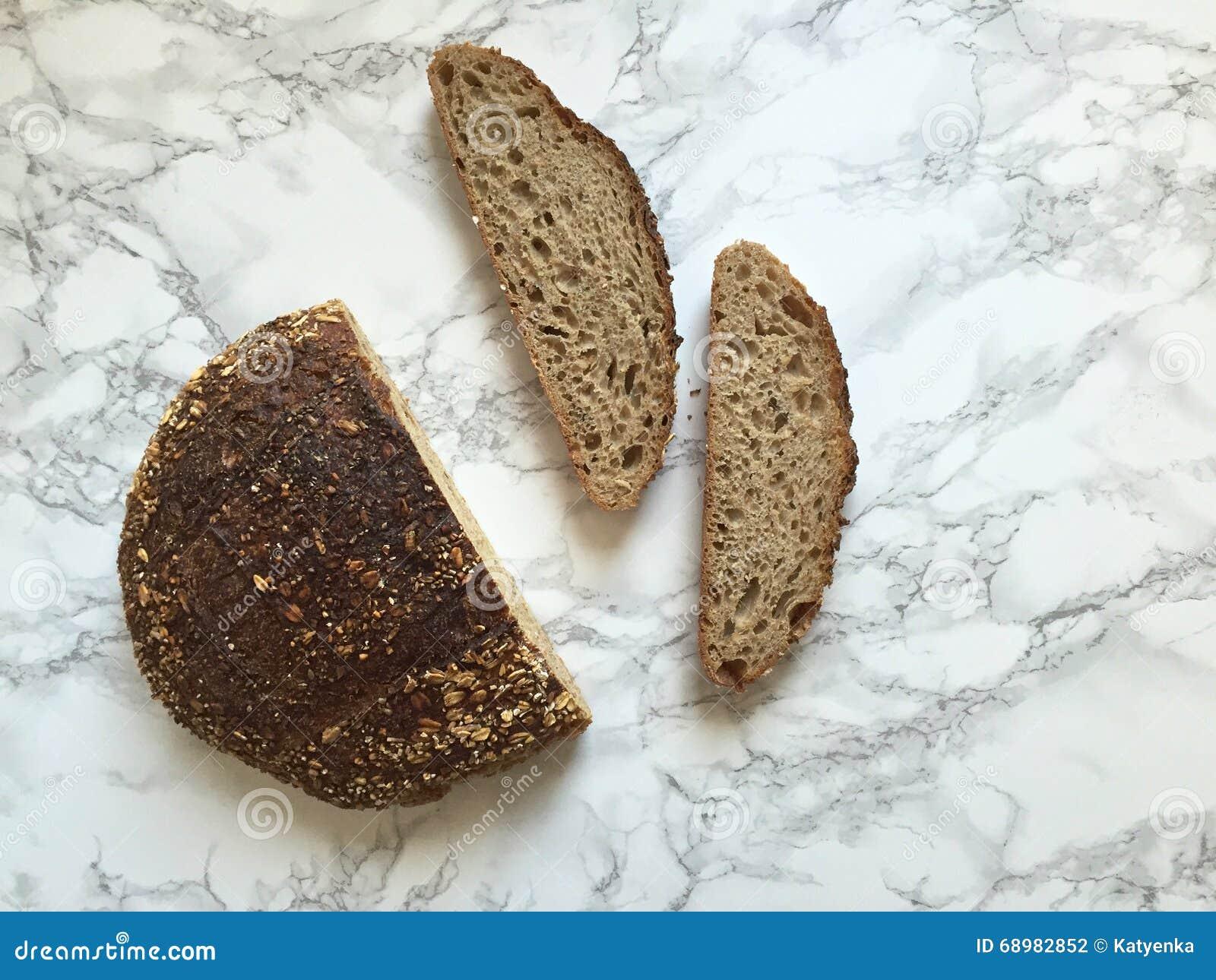 Χειρωνακτικές φραντζόλα και φέτες ψωμιού μαγιάς μαρμάρινο countertop