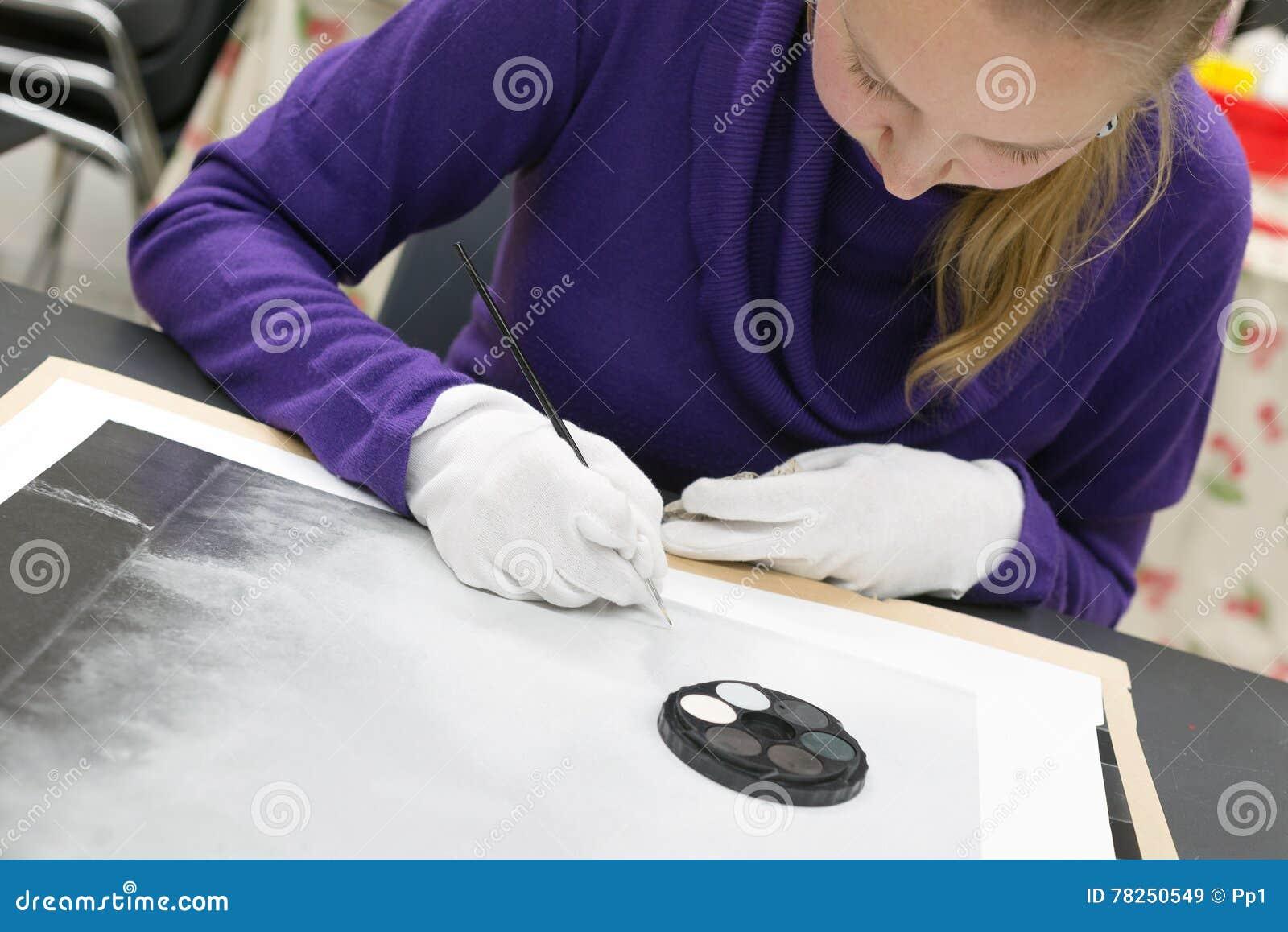 Χειρωνακτικό ρετουσάρισμα τυπωμένων υλών φωτογραφιών από τη γυναίκα με το μελάνι βουρτσών και χρωστικών ουσιών