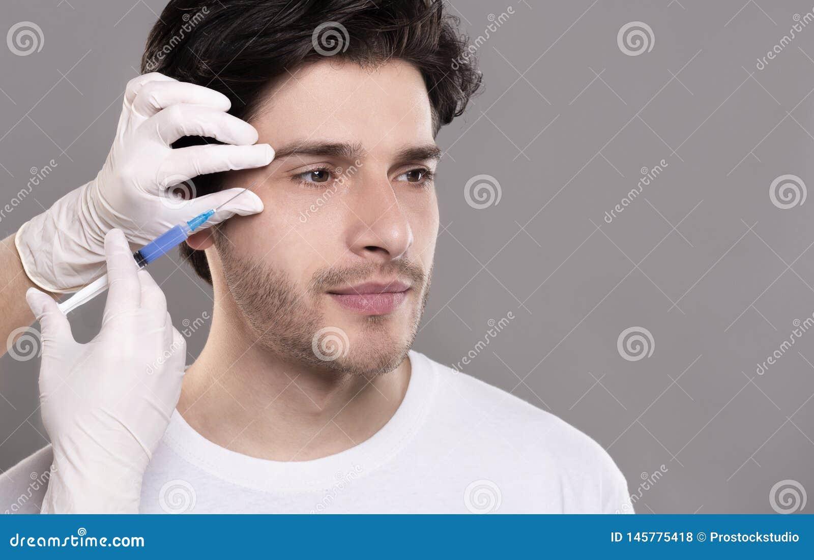 Χιλιετής τύπος που παίρνει την πλήρωση χειρουργικών επεμβάσεων των του προσώπου ρυτίδων