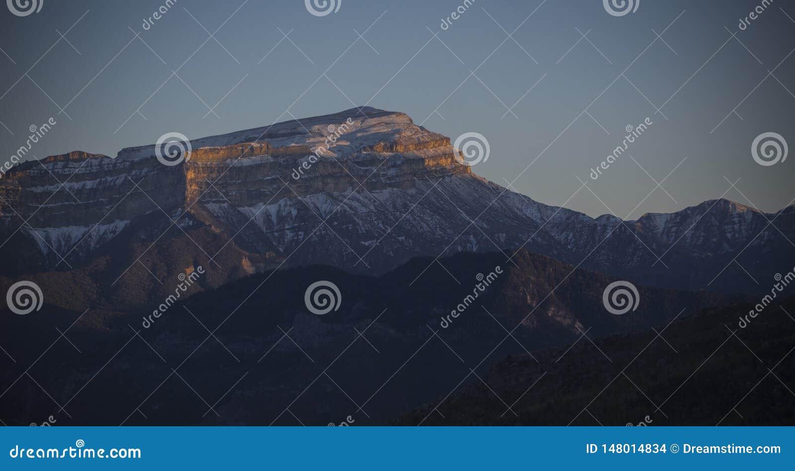 Χιονώδες βουνό Καύκασου στο ηλιοβασίλεμα