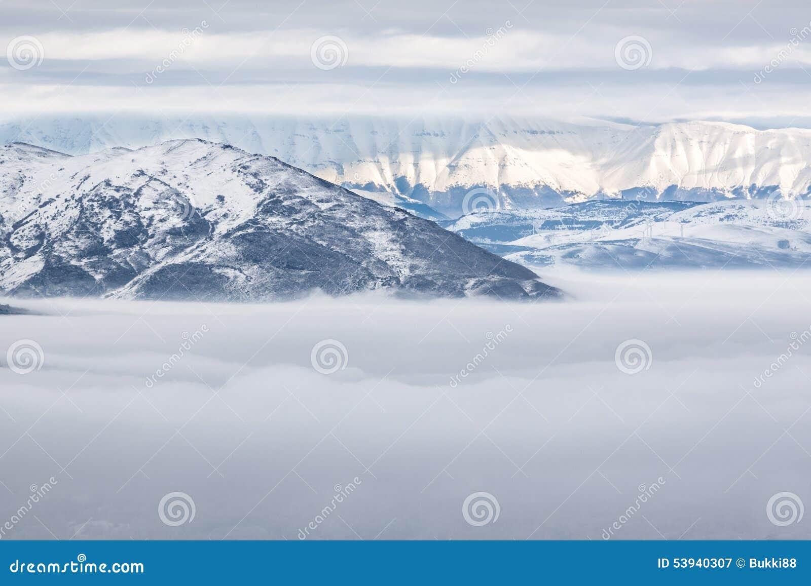Χιονώδη βουνά με την ομίχλη