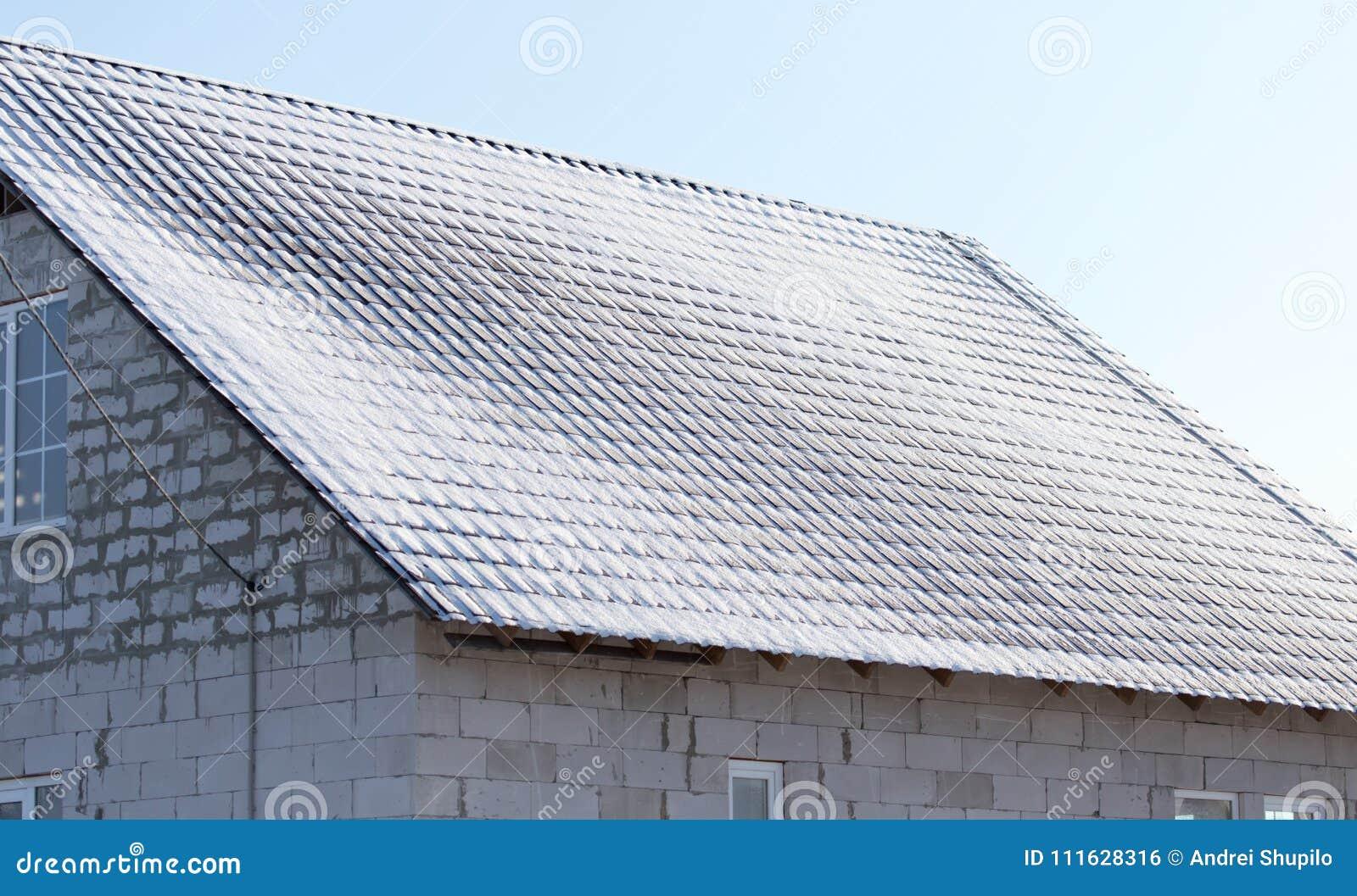 Χιόνι στη στέγη του σπιτιού το χειμώνα