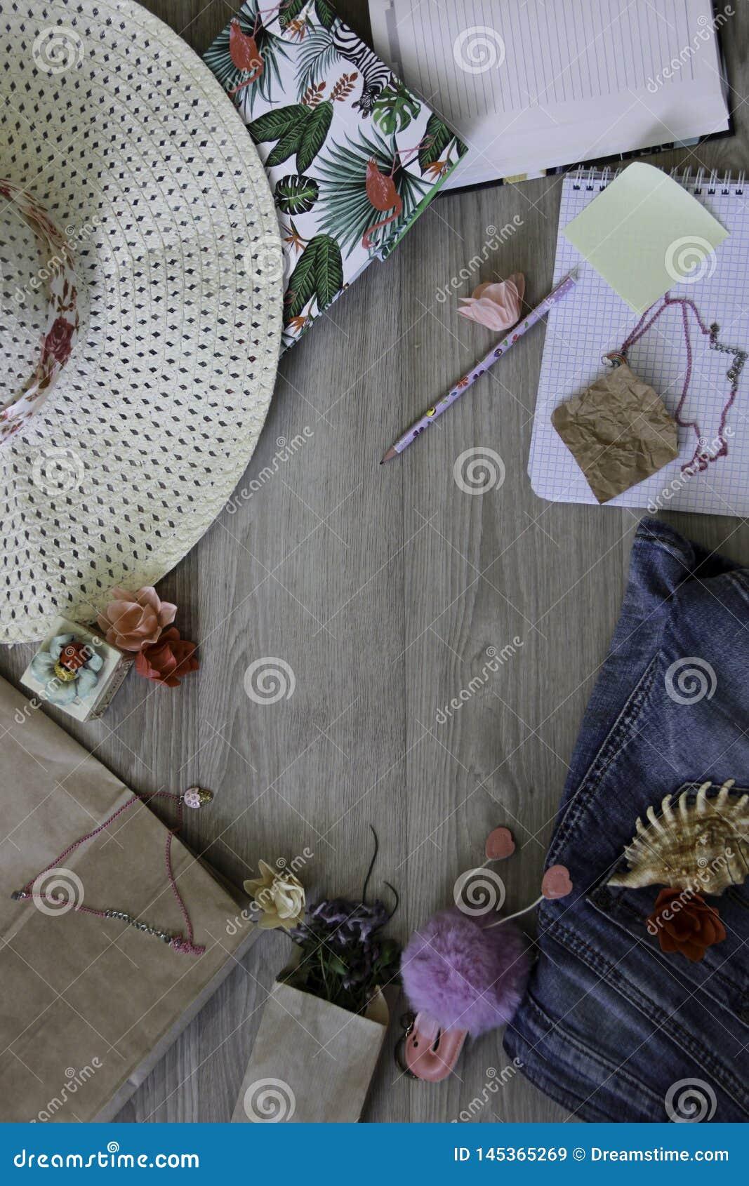 Χλεύη επάνω στο χώρο εργασίας με το καπέλο, τη μάνδρα, τα τζιν, το έγγραφο, το κρεμαστό κόσμημα, το κοχύλι, τα λουλούδια, το παιχ