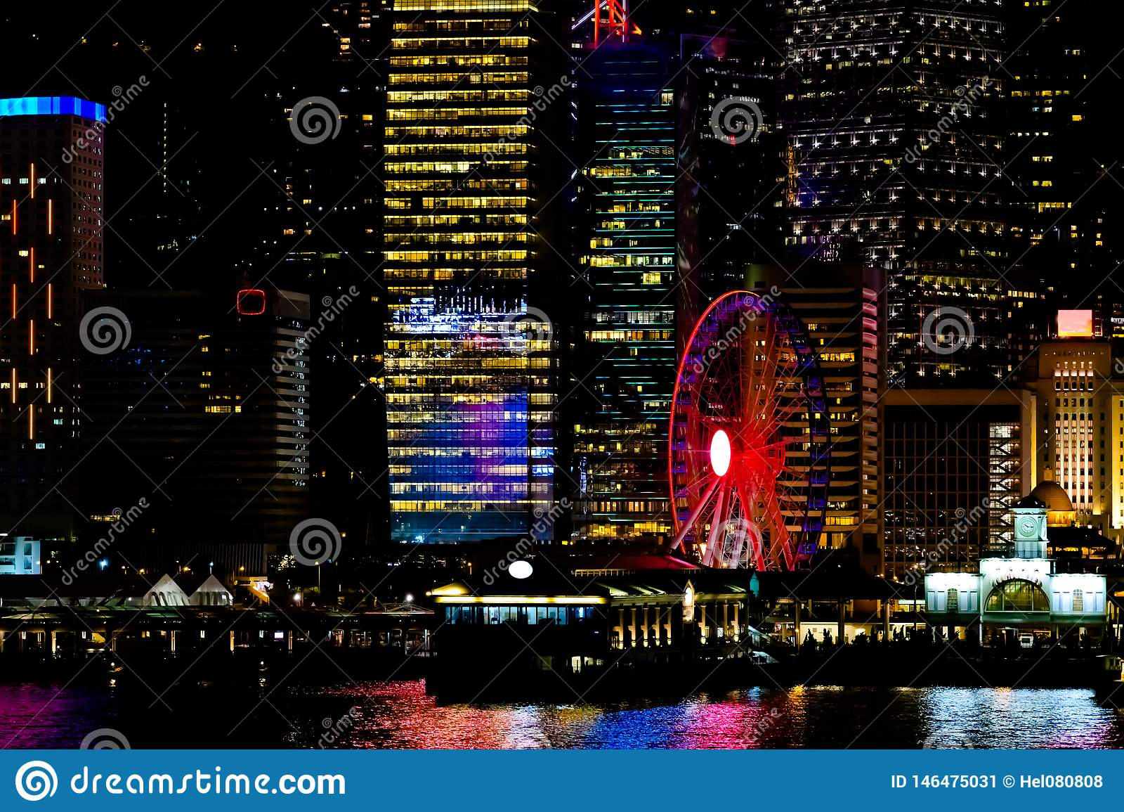 Χονγκ Κονγκ τη νύχτα Η κεντρική αποβάθρα, ferris κυλά, ζωηρόχρωμη διαφήμιση, κινεζικά ιδεογράμματα, όμορφες αντανακλάσεις