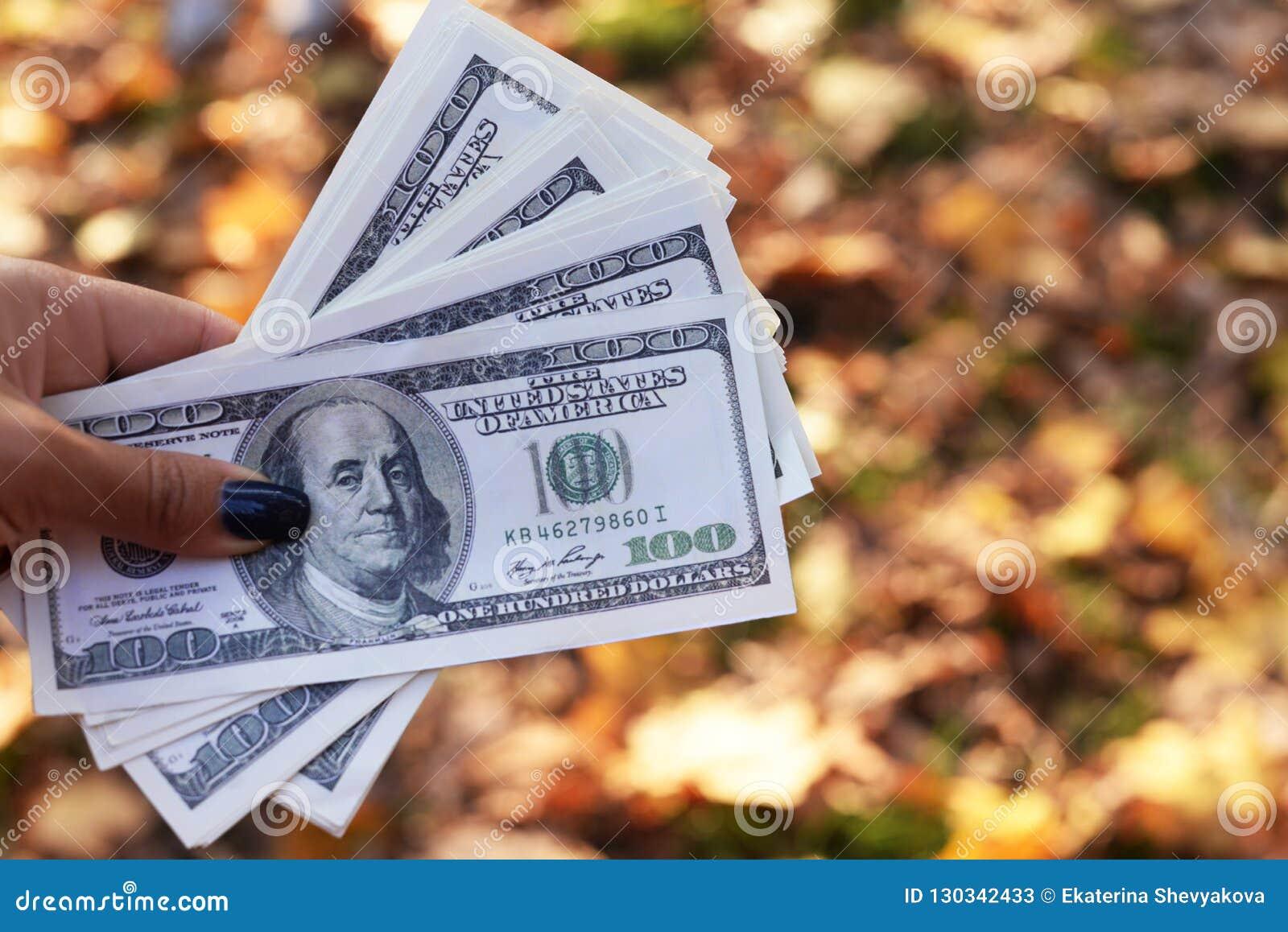 Χρήματα τραπεζογραμματίων εκατό δολάρια στο χέρι ενός κοριτσιού