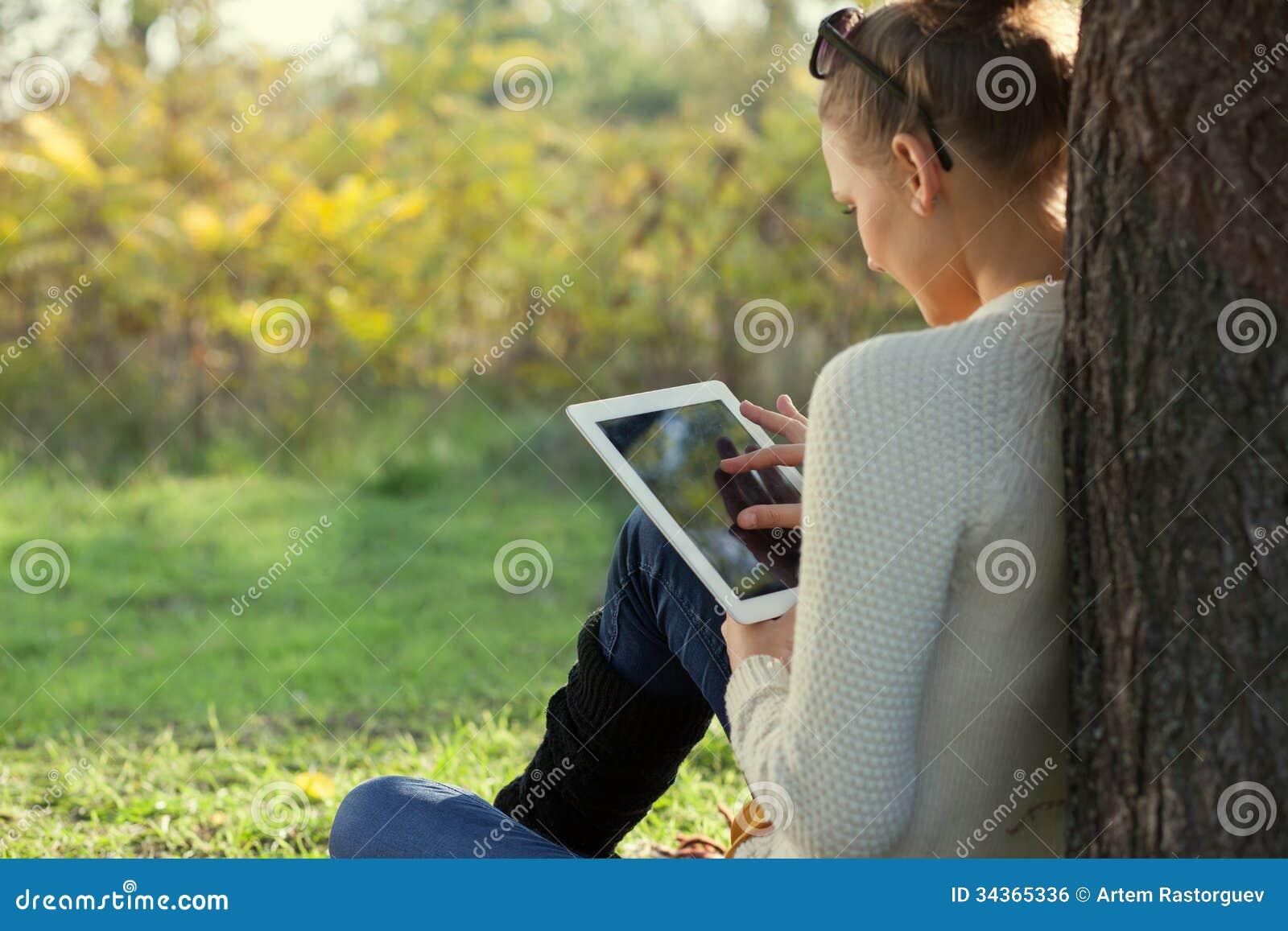 Χρησιμοποίηση ipad της νέας γυναίκας στο πάρκο