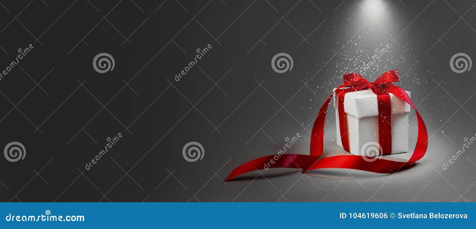 Χριστουγέννων δώρων άσπρο κιβωτίων κόκκινο κορδελλών σκοτεινό γκρίζο υποβάθρου έννοιας φωτισμένο νύχτα έμβλημα σύνθεσης διακοπών