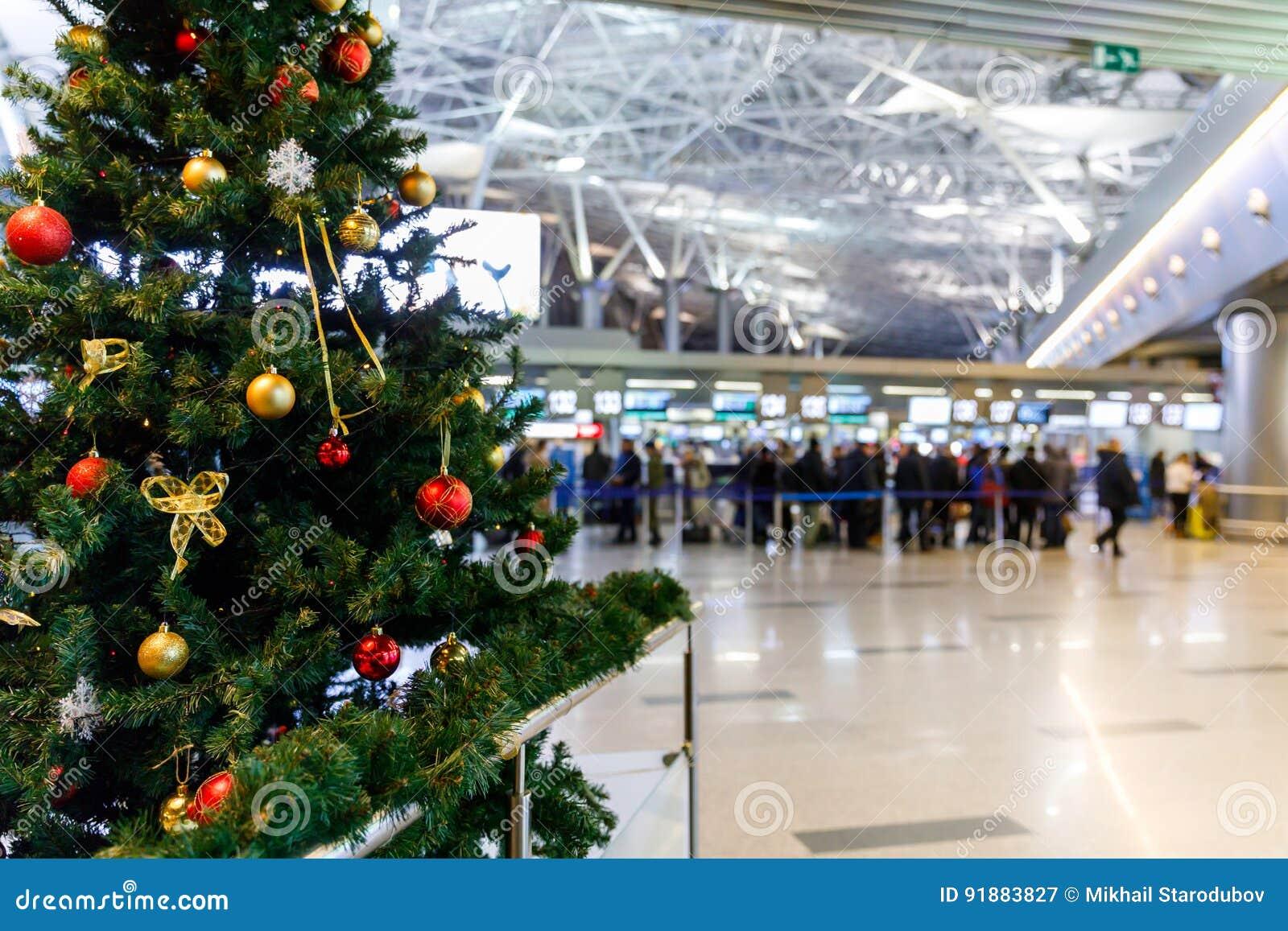 Χριστουγεννιάτικο δέντρο στον αερολιμένα και άνθρωποι στους μετρητές εισόδου