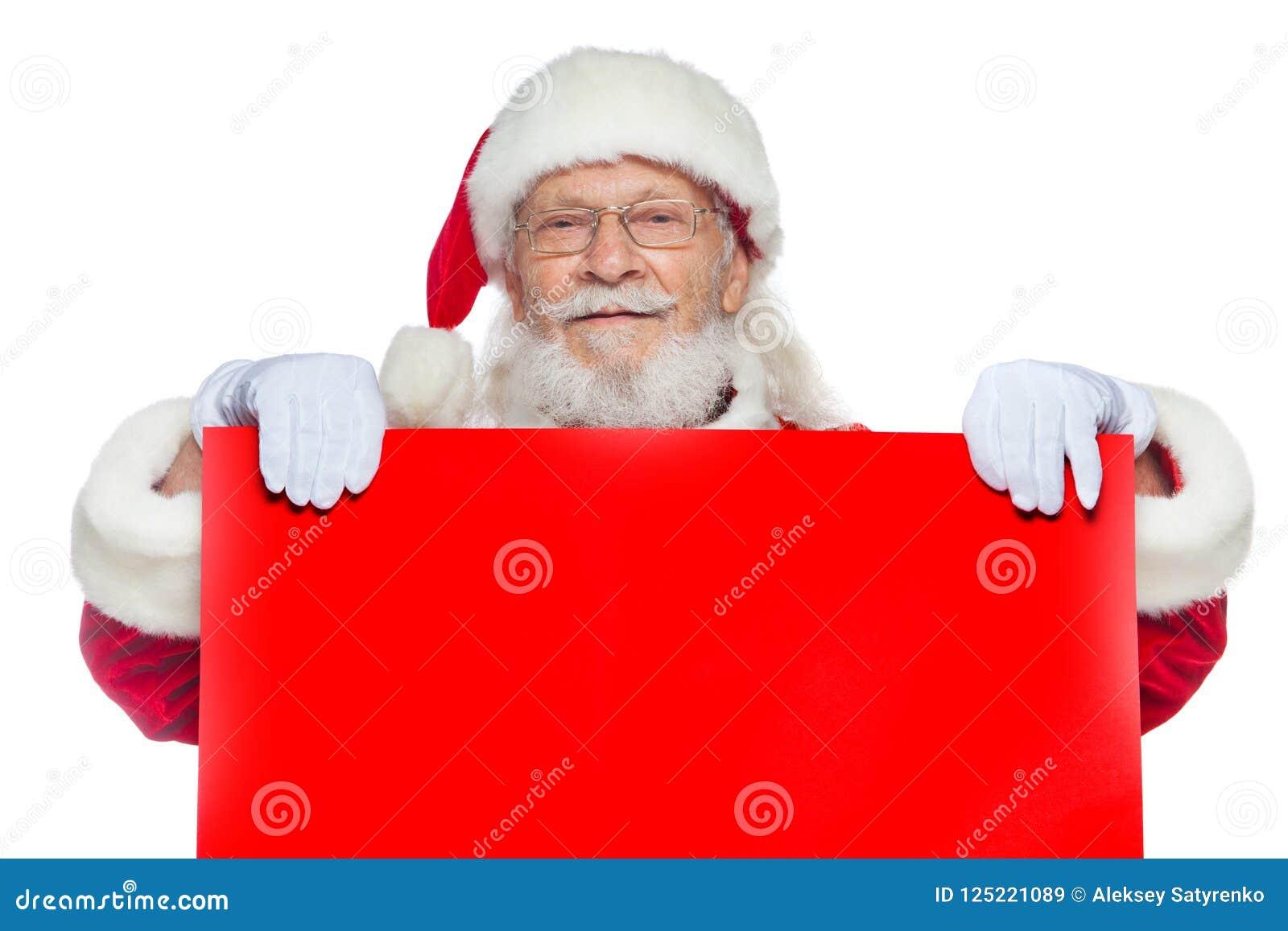 Χριστούγεννα Ο καλός Άγιος Βασίλης στα άσπρα γάντια κρατά ένα κενό χαρτόνι του κόκκινου χρώματος Θέση για τη διαφήμιση, για το κε