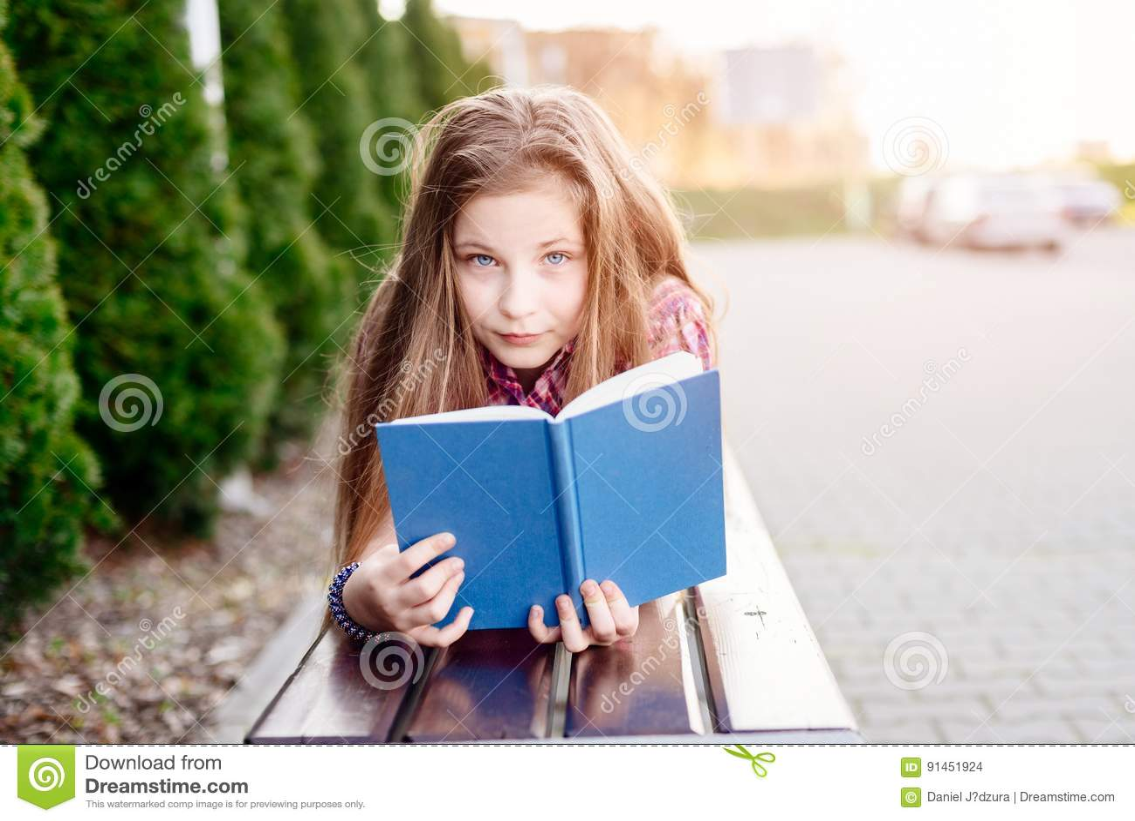 b1aa2378324 Χρονών ξανθό βιβλίο ανάγνωσης κοριτσιών μπλε ματιών τα δέκα στον πάγκο.  Περισσότερες παρόμοιες στοκ εικόνες