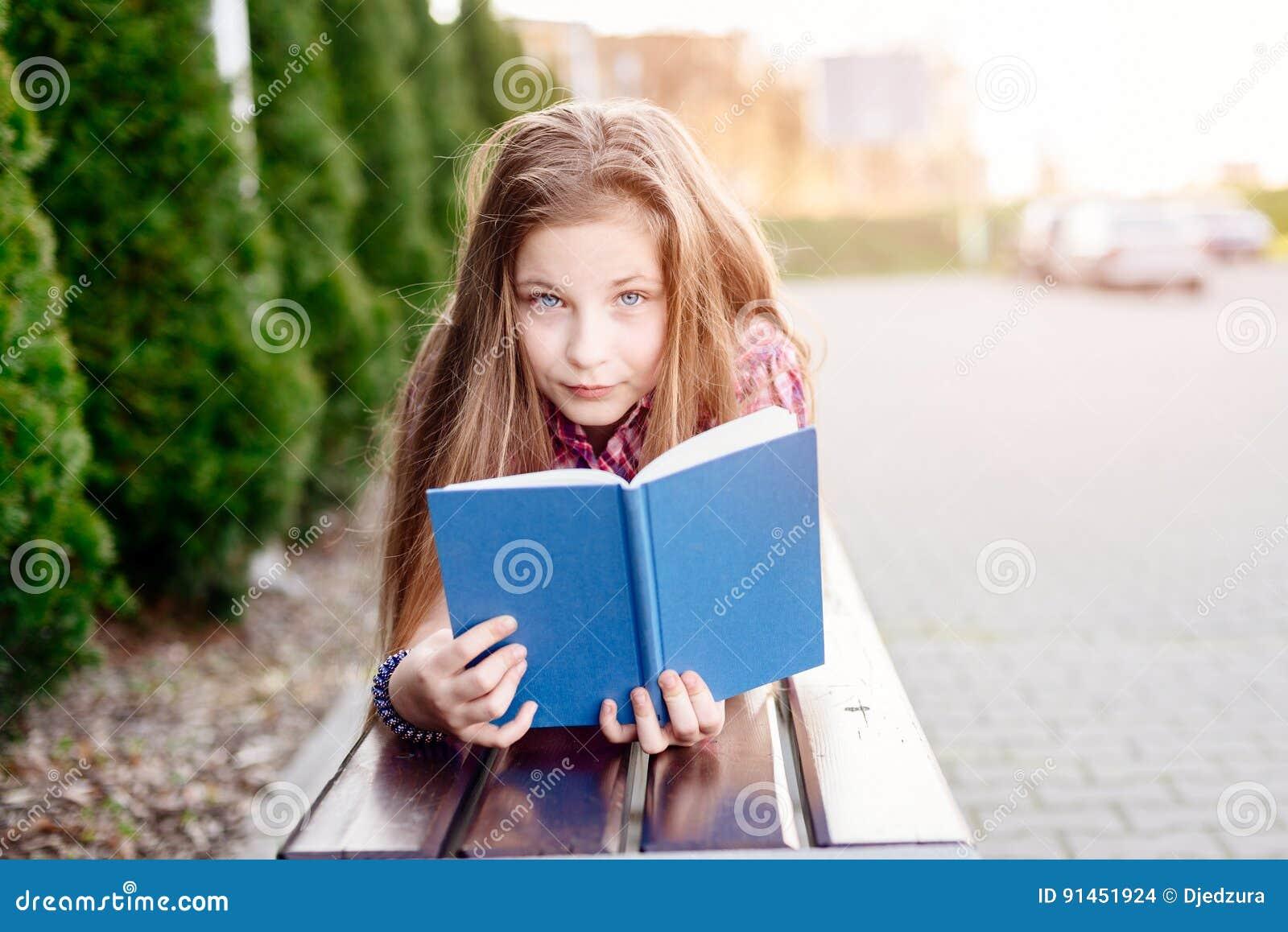 57b30feaded Χρονών ξανθό βιβλίο ανάγνωσης κοριτσιών μπλε ματιών τα δέκα στον πάγκο.  Περισσότερες παρόμοιες στοκ εικόνες