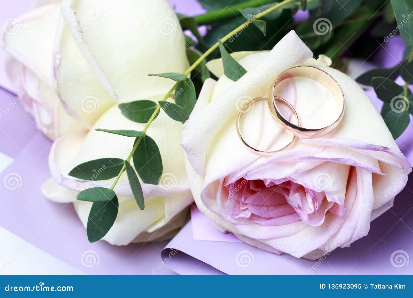 Χρυσά γαμήλια δαχτυλίδια σε μια ανθοδέσμη των τριαντάφυλλων, γαμήλια έννοια