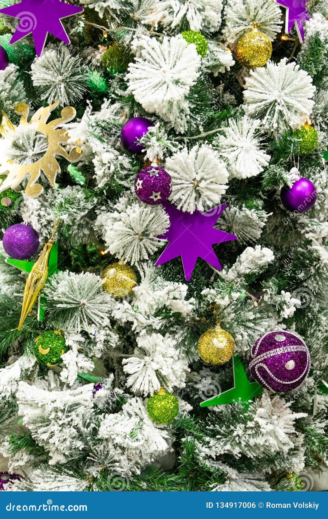 Χρυσά και ιώδη σφαίρες και αστέρια στο χριστουγεννιάτικο δέντρο Φωτεινό αφηρημένο υπόβαθρο για το σχέδιο του νέου έτους και