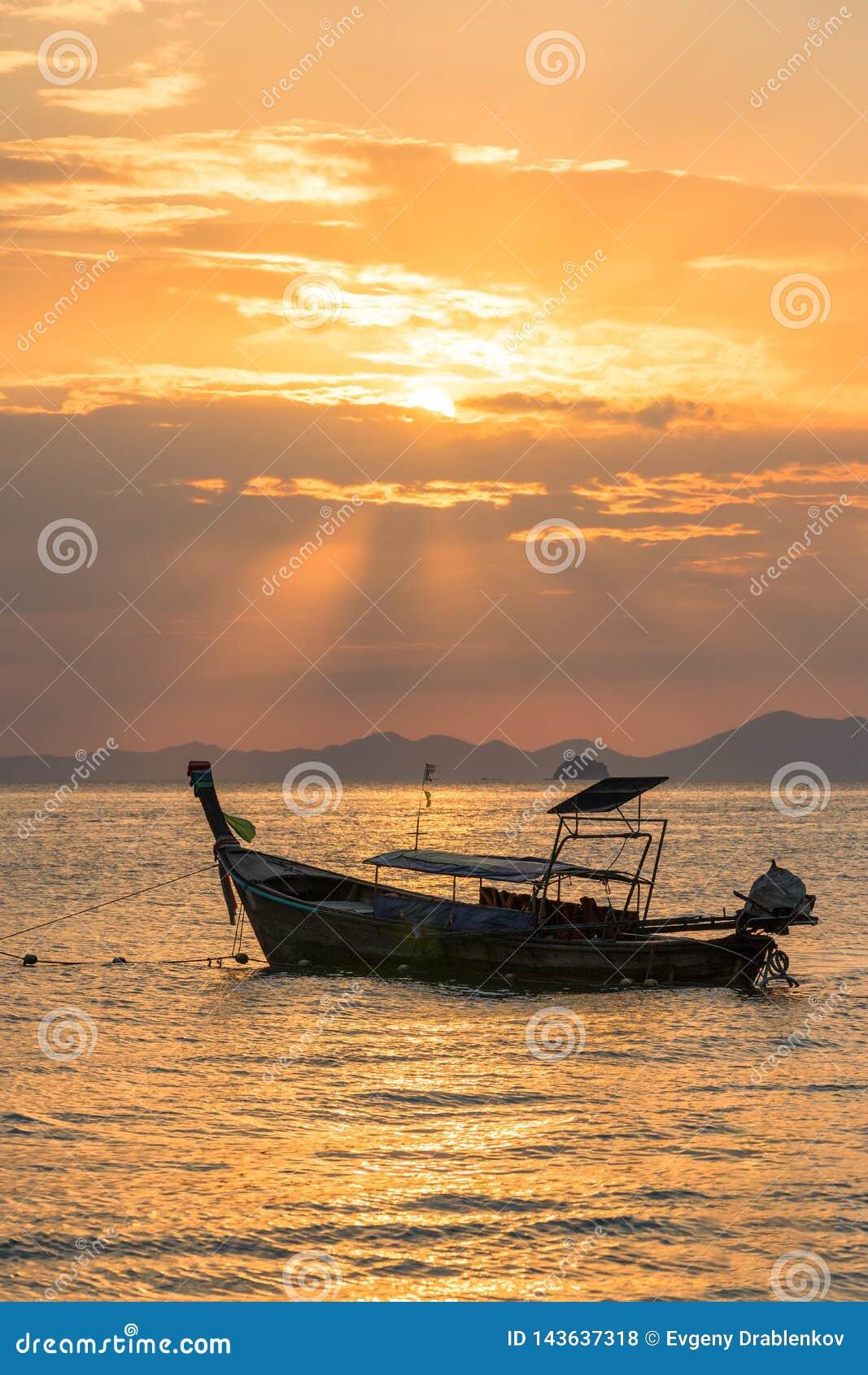 Χρυσές ακτίνες ήλιων και τοπική κενή ταϊλανδική βάρκα longtail κάτω από τους στο θαλάσσιο νερό στο όμορφο πορτοκαλί ηλιοβασίλεμα