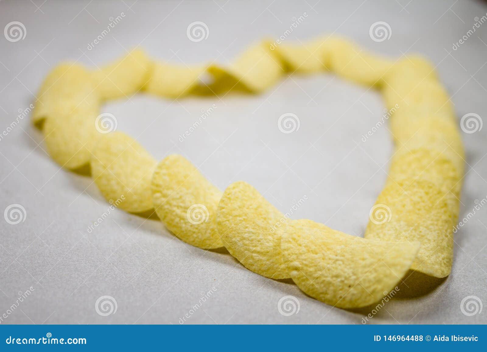 Χρυσή σύνθεση σχηματισμού καρδιών τσιπ πατατών που απομονώνεται πέρα από το ανοικτό γκρι γκρίζο άσπρο υπόβαθρο