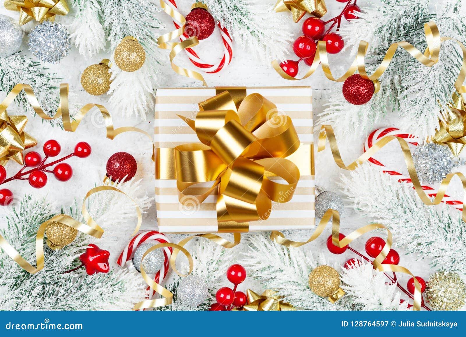Χρυσό δώρο ή παρόν κιβώτιο, χιονώδεις δέντρο έλατου και διακοσμήσεις Χριστουγέννων στην άσπρη ξύλινη άποψη επιτραπέζιων κορυφών Ε