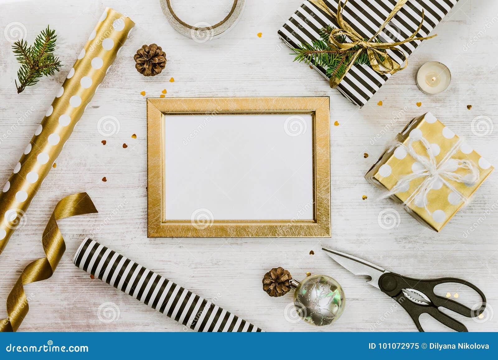 Χρυσό πλαίσιο ptoto, κιβώτια δώρων, παιχνίδια κώνων πεύκων και Χριστουγέννων και τυλίγοντας υλικά σε ένα άσπρο ξύλινο παλαιό υπόβ