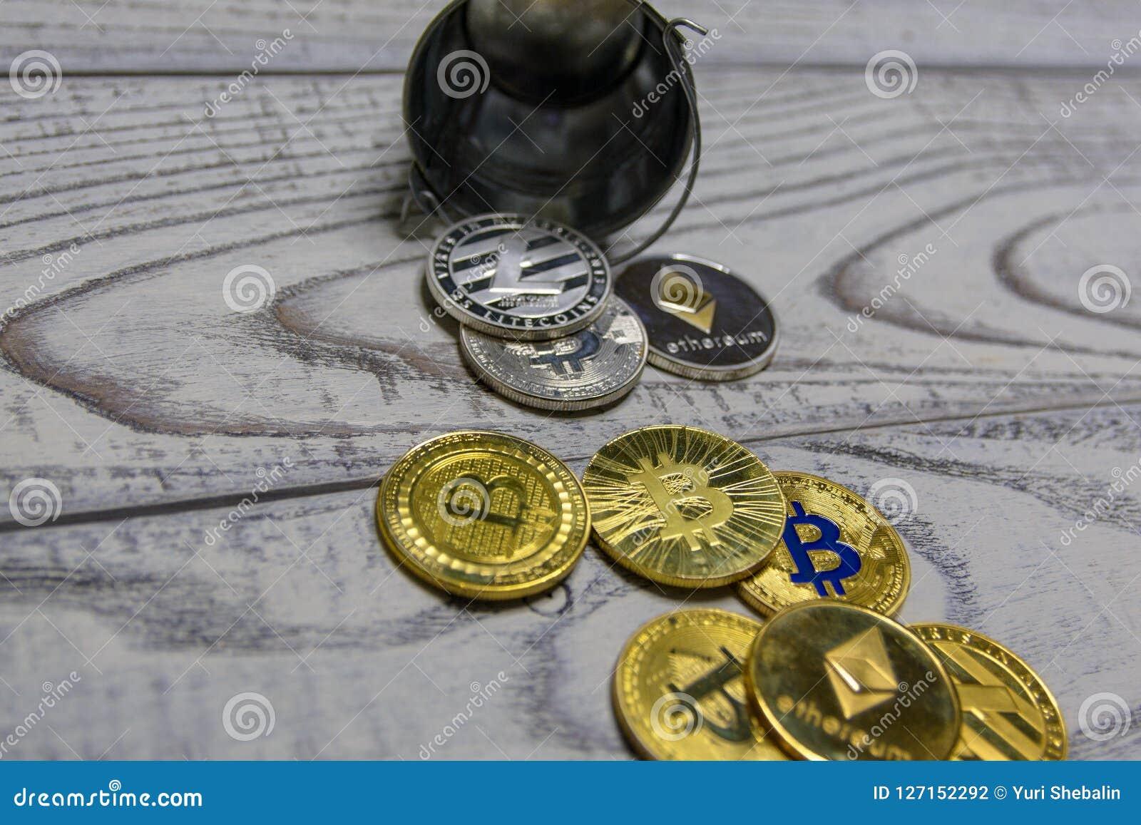 Χρυσό bitcoin και άλλο crypto νόμισμα στην πεσμένη κινηματογράφηση σε πρώτο πλάνο κάδων μετάλλων παιχνιδιών
