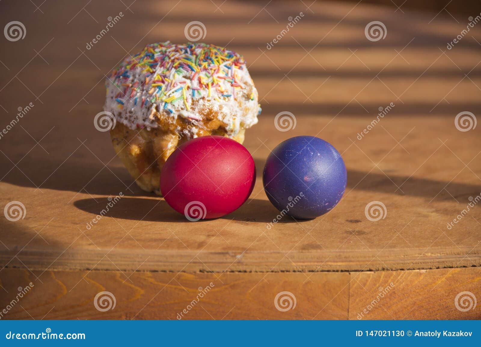 Χρωματισμένα αυγά και κέικ σε έναν ξύλινο πίνακα