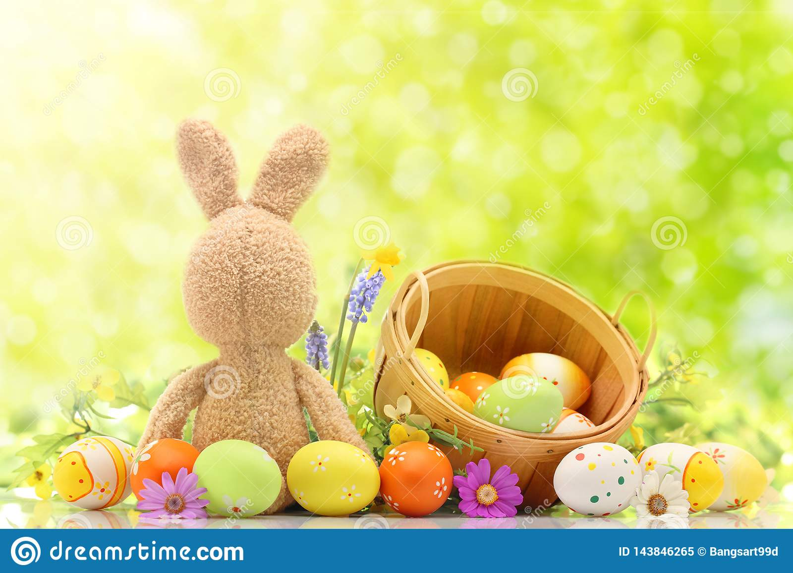 Χρωματισμένα αυγά Πάσχας με το κουνέλι και το καλάθι λαγουδάκι στη μέση του πράσινου υποβάθρου Ελεύθερου χώρου για το κείμενο
