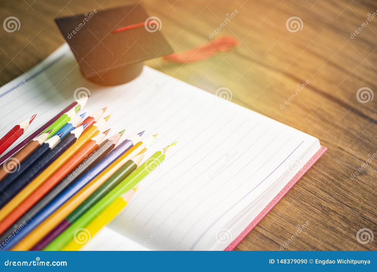 Χρωματισμένες σύνολο και βαθμολόγηση ΚΑΠ μολυβιών στο σημειωματάριο της Λευκής Βίβλου πίσω στο σχολείο και την έννοια εκπαίδευσης