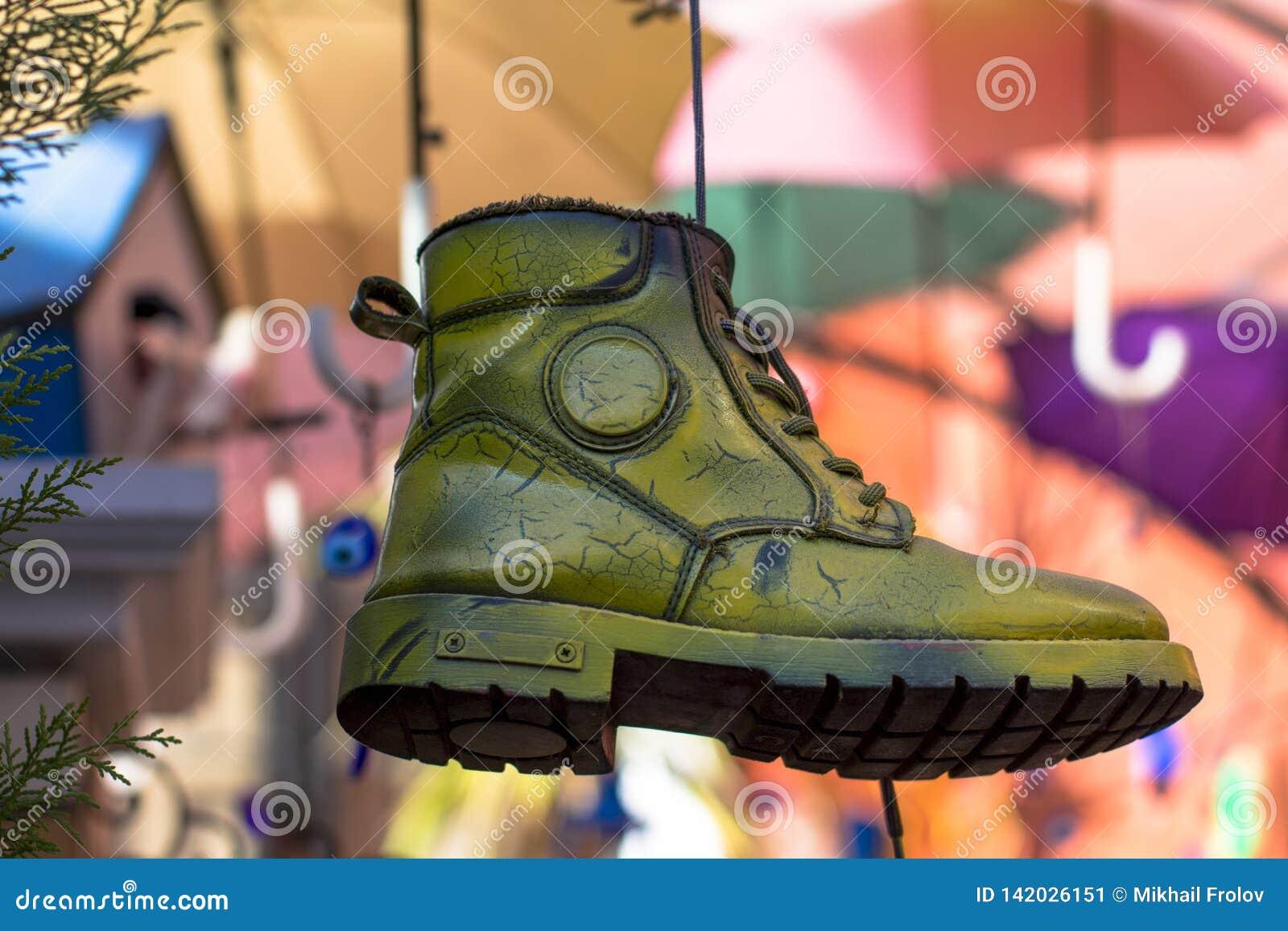 Χρωματισμένη ένωση παπουτσιών σε ένα σκοινί Φωτεινή και ζωηρόχρωμη σύνθεση μπότα - αφαίρεση σε ένα θολωμένο υπόβαθρο