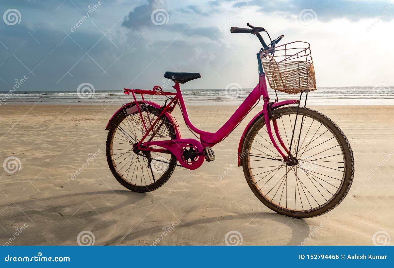 Χρωματισμένο ροζ ποδήλατο ηλικιωμένων κυριών που σταθμεύουν στην παραλία μετά από να ανακυκλώσει Μια διασκέδαση γέμισε την υγιή δ