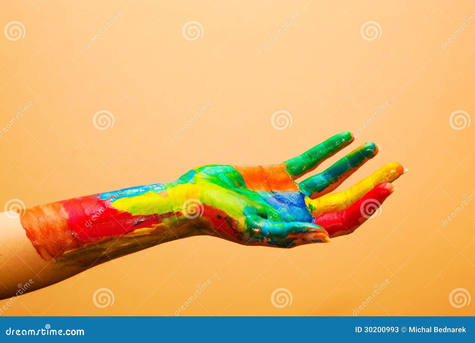 Χρωματισμένο χέρι, ζωηρόχρωμη διασκέδαση. Πορτοκαλί υπόβαθρο