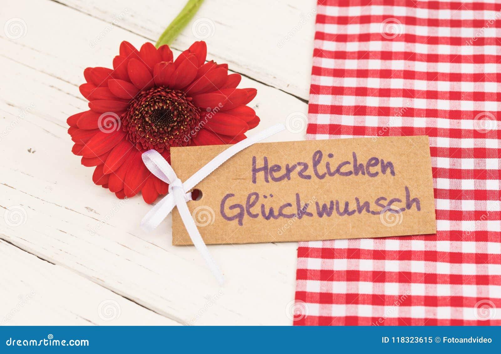 Χρόνια πολλά ευχετήρια κάρτα, με το γερμανικό κείμενο Herzlichen Glueckwunsch και το κόκκινο λουλούδι μαργαριτών gerbera