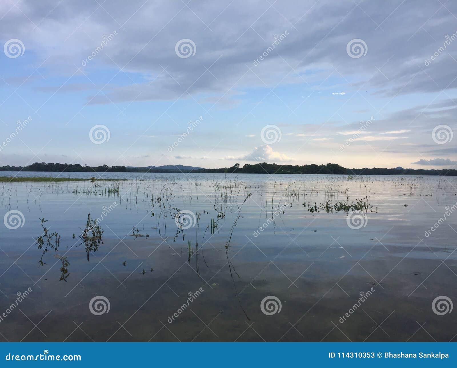 Χρόνος ηλιοβασιλέματος πλησίον σε μια λίμνη