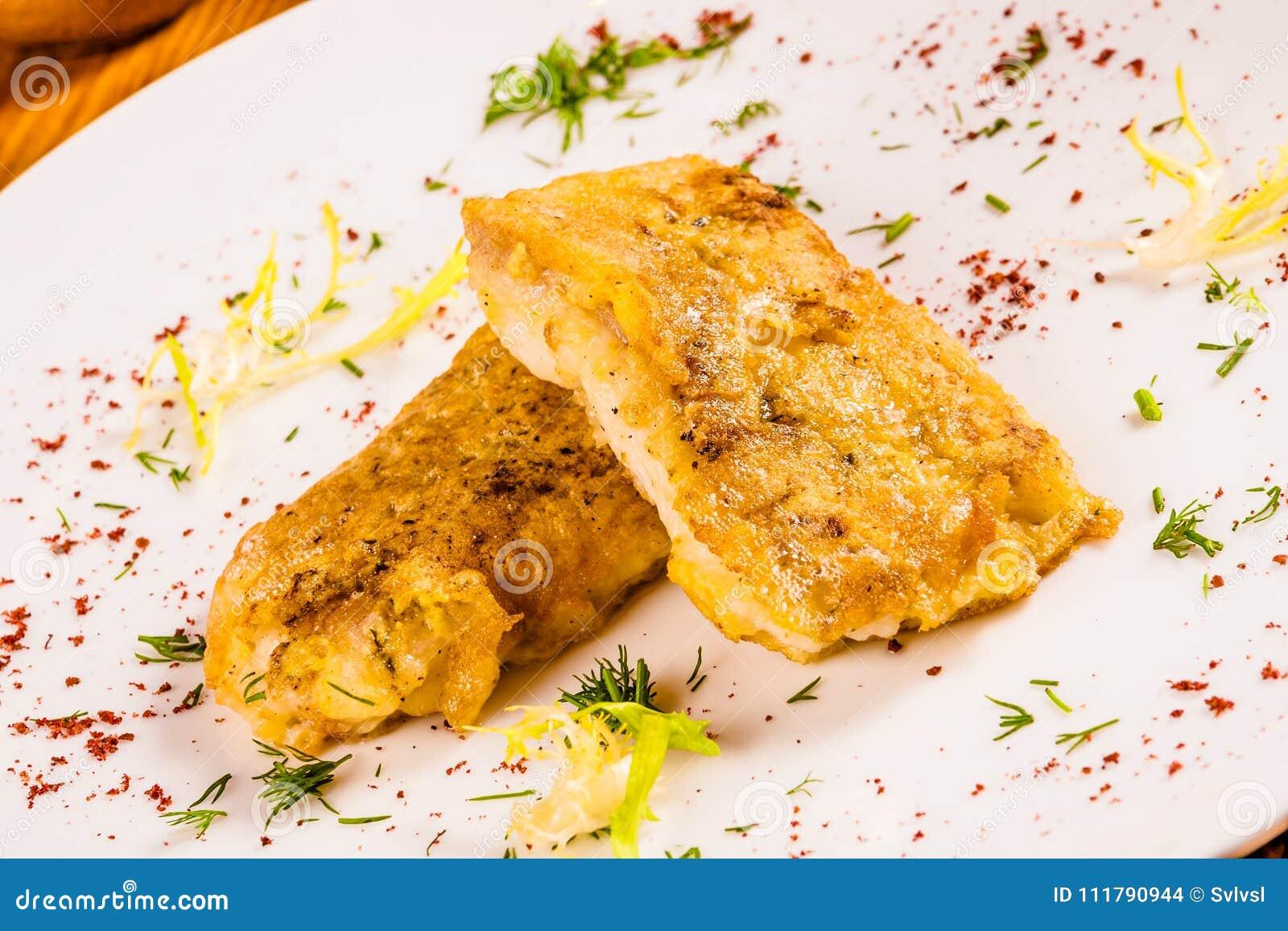 Χτυπημένα ψάρια με τα καρυκεύματα στο άσπρο πιάτο
