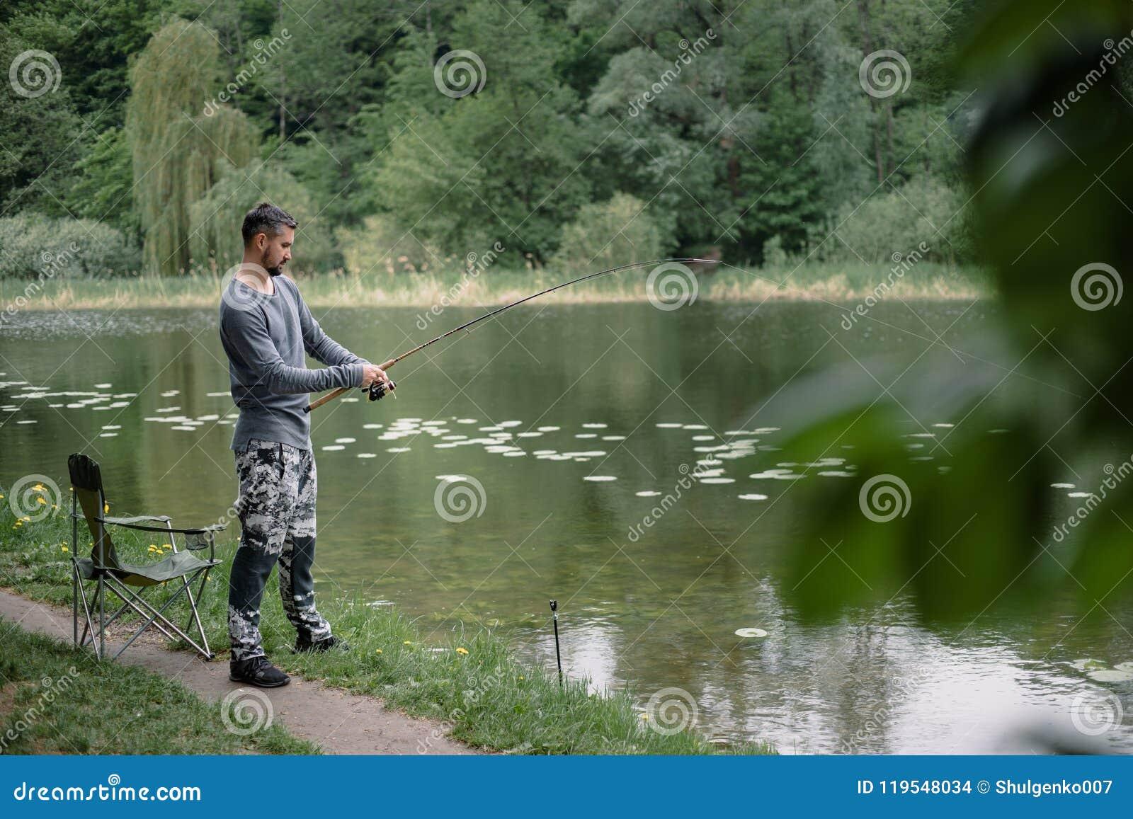 Χυτή ψαράς ράβδος αλιείας στη λίμνη ή το νερό ποταμού Άτομο με την περιστροφή του εξοπλισμού στον πράσινο δασικό υγιή τρόπο ζωής