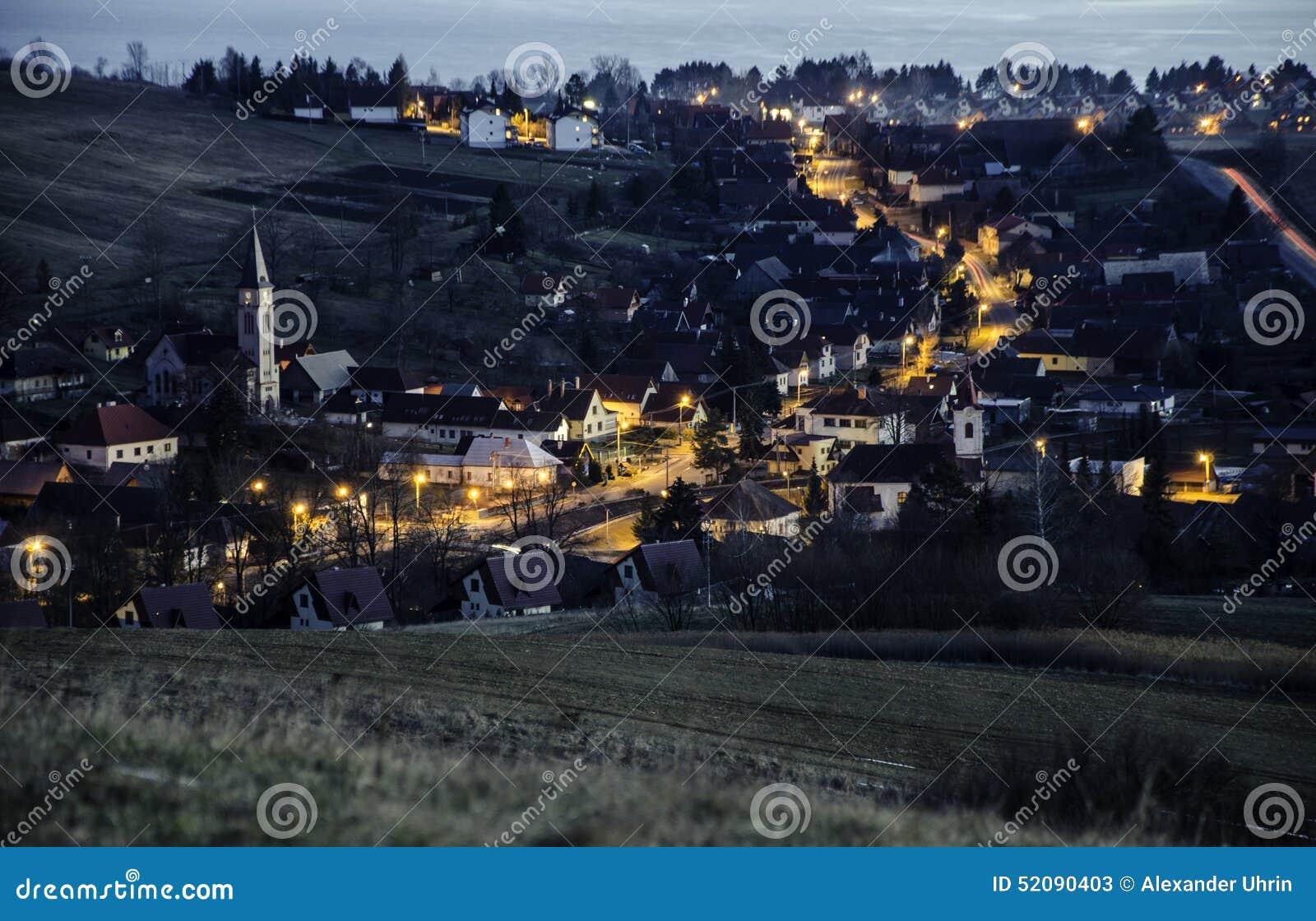 Χωριό νύχτας μετά από το ηλιοβασίλεμα στην κυρίαρχη εκκλησία κοντά σε Liptovsky MikulaÅ ¡