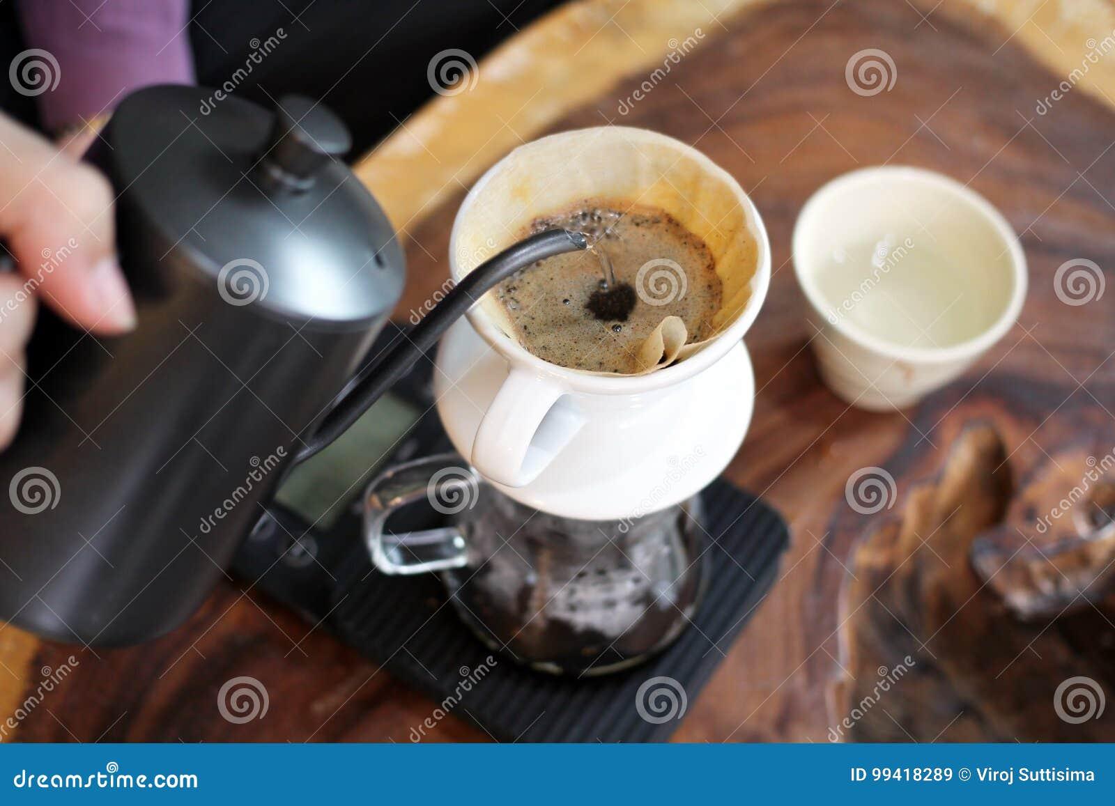 Χύνοντας ζεστό νερό Barista πέρα από τους λόγους καφέ που κάνουν τη σταλαγματιά να παρασκευάσει τον καφέ