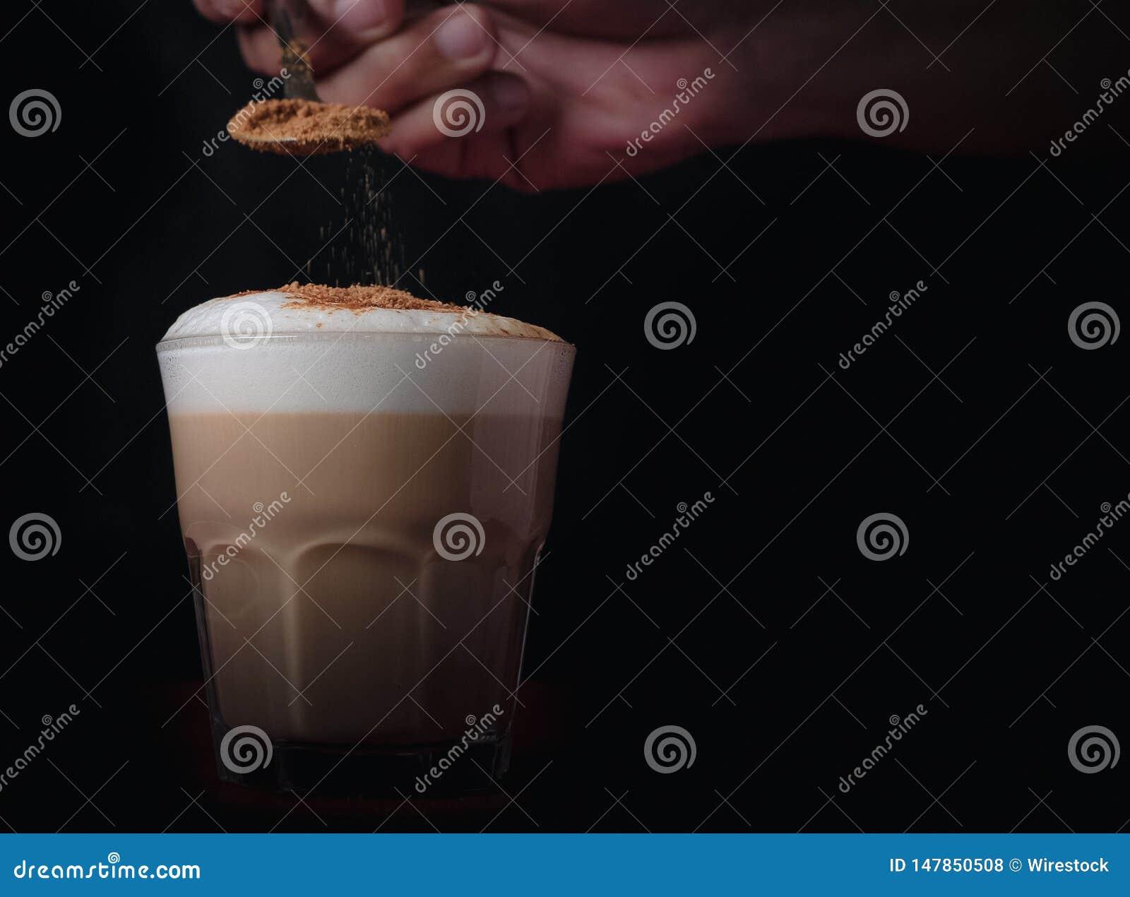 Χύνοντας κανέλα σε έναν καλοφτιαγμένο foamy καφέ με το διάστημα για το κείμενο