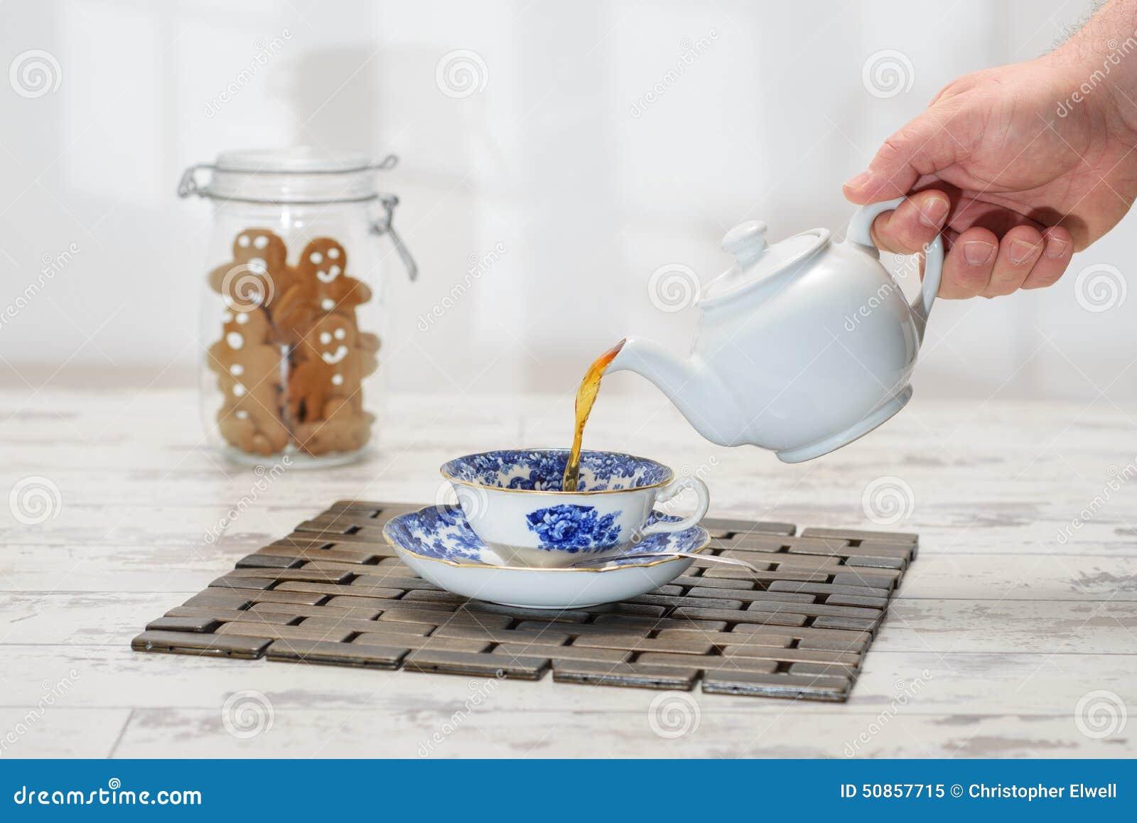 χύνοντας τσάι φλυτζανιών