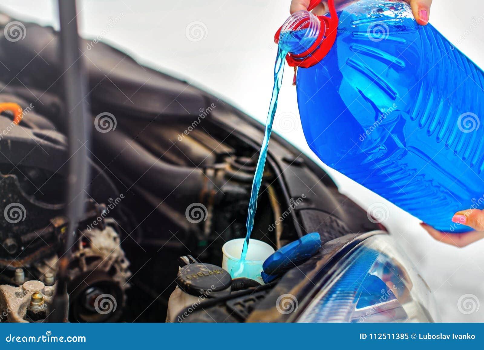 Χύνοντας υγρό πλυσίματος οθόνης αυτοκινήτων αντιψυκτικού γυναικών στο βρώμικο αυτοκίνητο