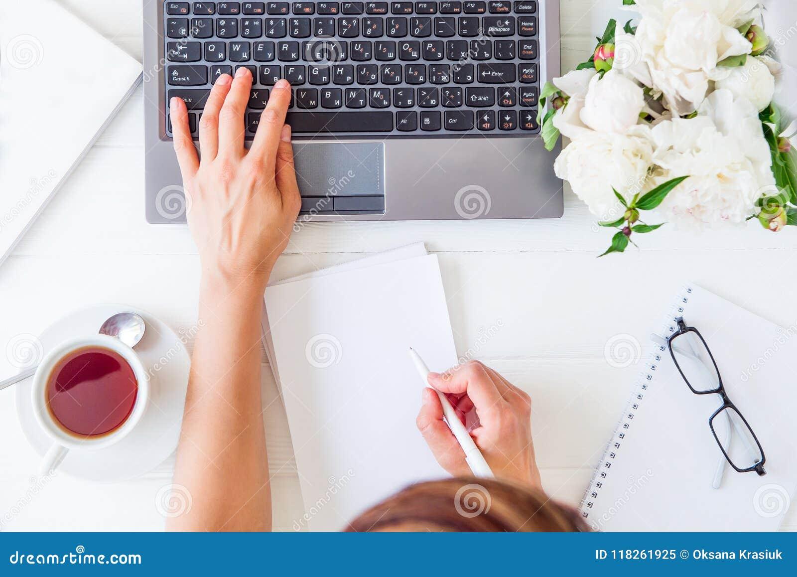 Χώρος εργασίας με το χέρι κοριτσιών ` s στο πληκτρολόγιο lap-top και γράψιμο στο σημειωματάριο με το κενό κενό, φλυτζάνι του τσαγ