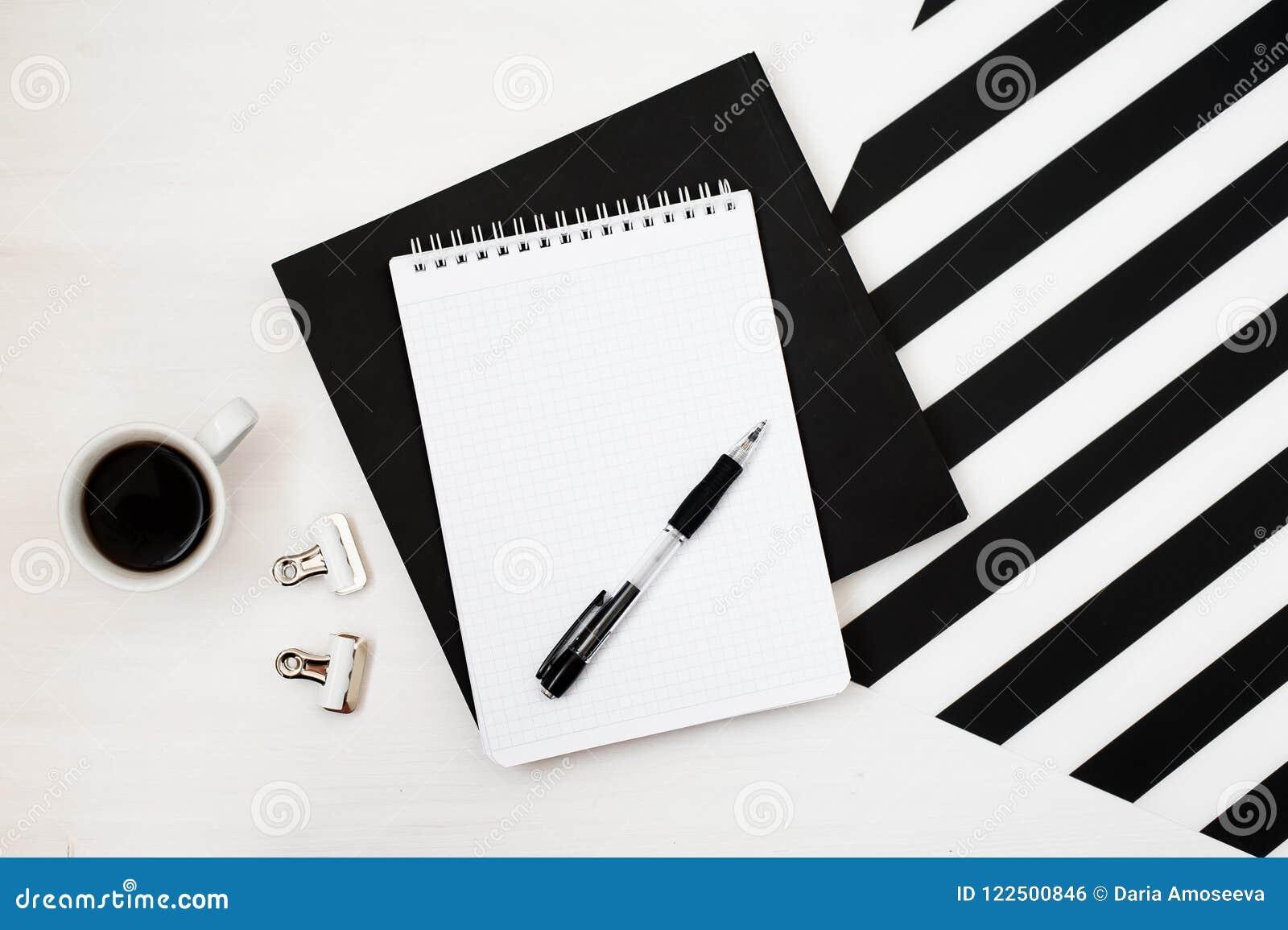 Χώρος εργασίας Minimalistic με το βιβλίο, σημειωματάριο, μολύβι, φλιτζάνι του καφέ στο ριγωτό γραπτό υπόβαθρο Επίπεδος βάλτε τη τ