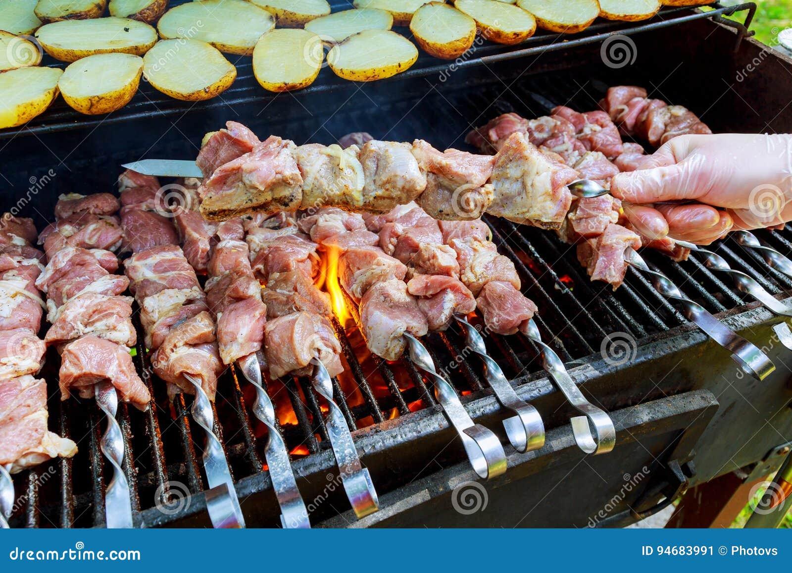Ψήσιμο στη σχάρα του κρέατος σχαρών στον ξύλινο άνθρακα Το άτομο μαγειρεύει το ορεκτικό καυτό shish kebab στα οβελίδια μετάλλων