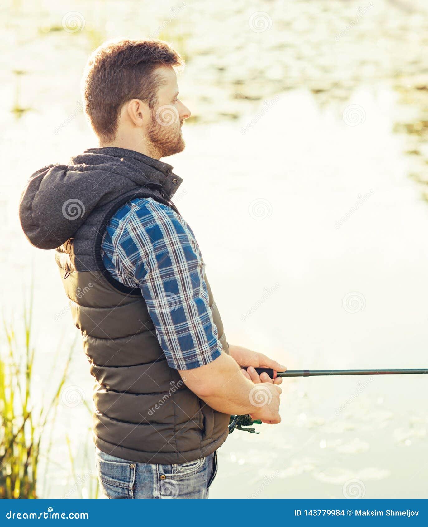 Ψαράς με μια περιστροφή και ένα δόλωμα που πιάνουν τα ψάρια σε μια λίμνη ή έναν ποταμό Άτομο σε ένα Σαββατοκύριακο με έναν δρόμο